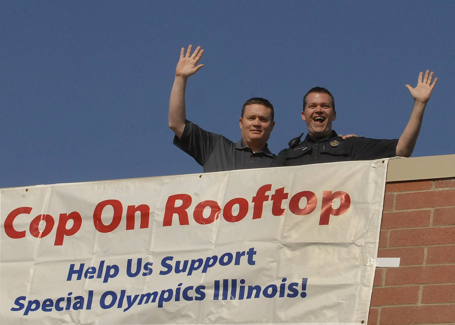 Commander Mike Zeigler, left, and Officer Pete Woolsey work the Sutton Road Dunkin' Donuts for the Cops on a Rooftop campaign. Officers got onto the rooftops at 5 a.m.
