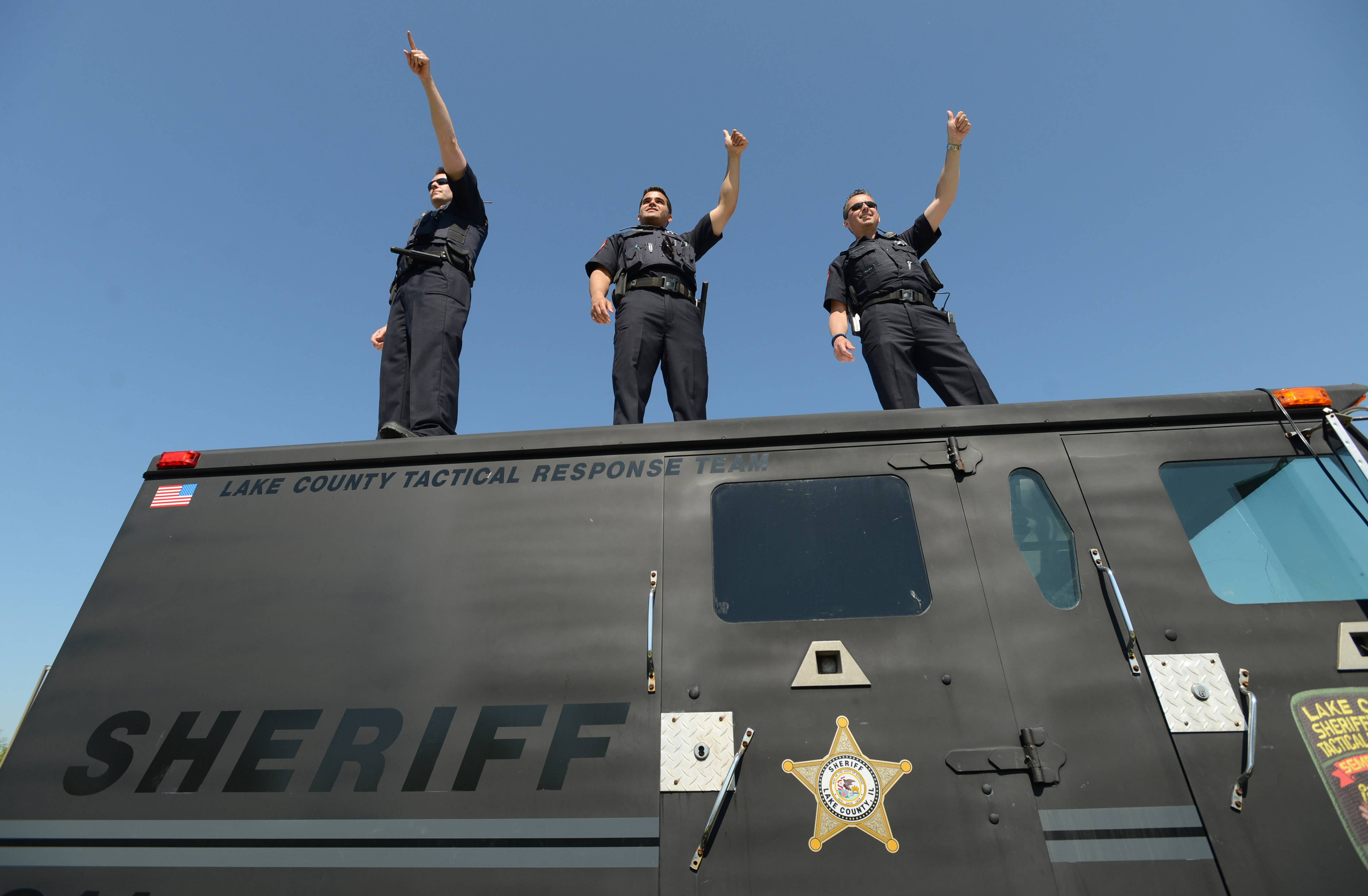 Lake County sheriff reserve deputies from Brian Hansen, left, Keith Salas and Thomas Kajohn wave from outside the Third Lake Dunkin' Donuts during Friday's Cop on Rooftop event. Twenty members of the sheriff's office raised money for the Law Enforcement Torch Run to benefit Special Olympics Illinois.