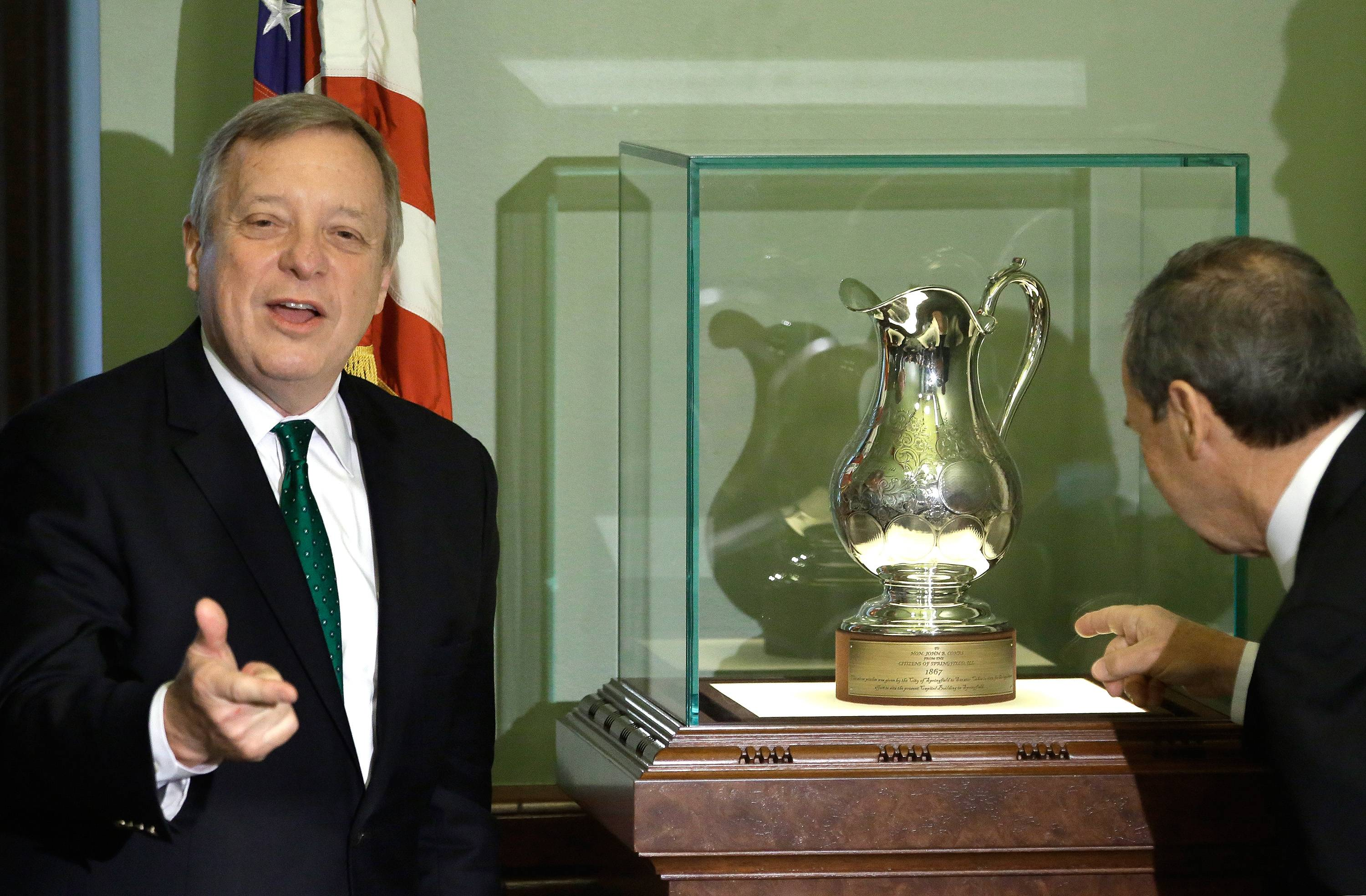 U.S. Sen. Dick Durbin, left, presents a silver pitcher that had been absent from the state for nearly 150 years. On the right is Illinois Senate President John Cullerton.
