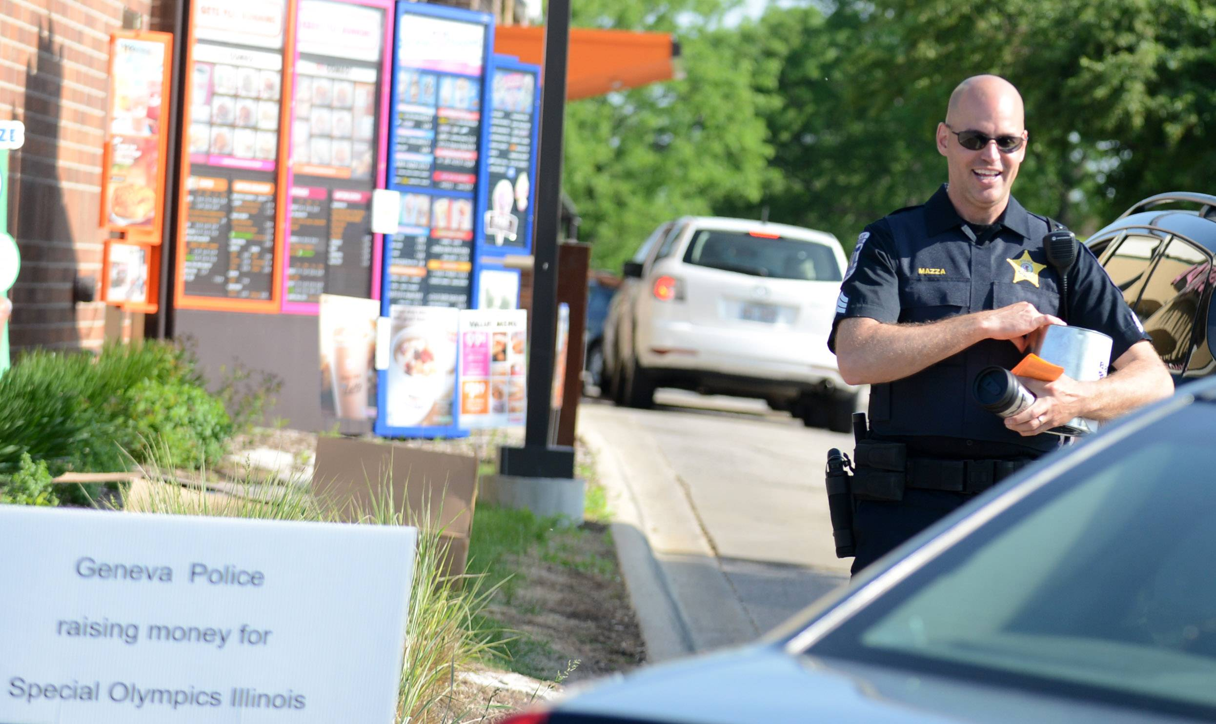 Batavia Police Sgt. Shawn Mazza collects donations for Special Olympics during the Cop on a Rooftop fundraiser at Dunkin Donuts in Batavia .