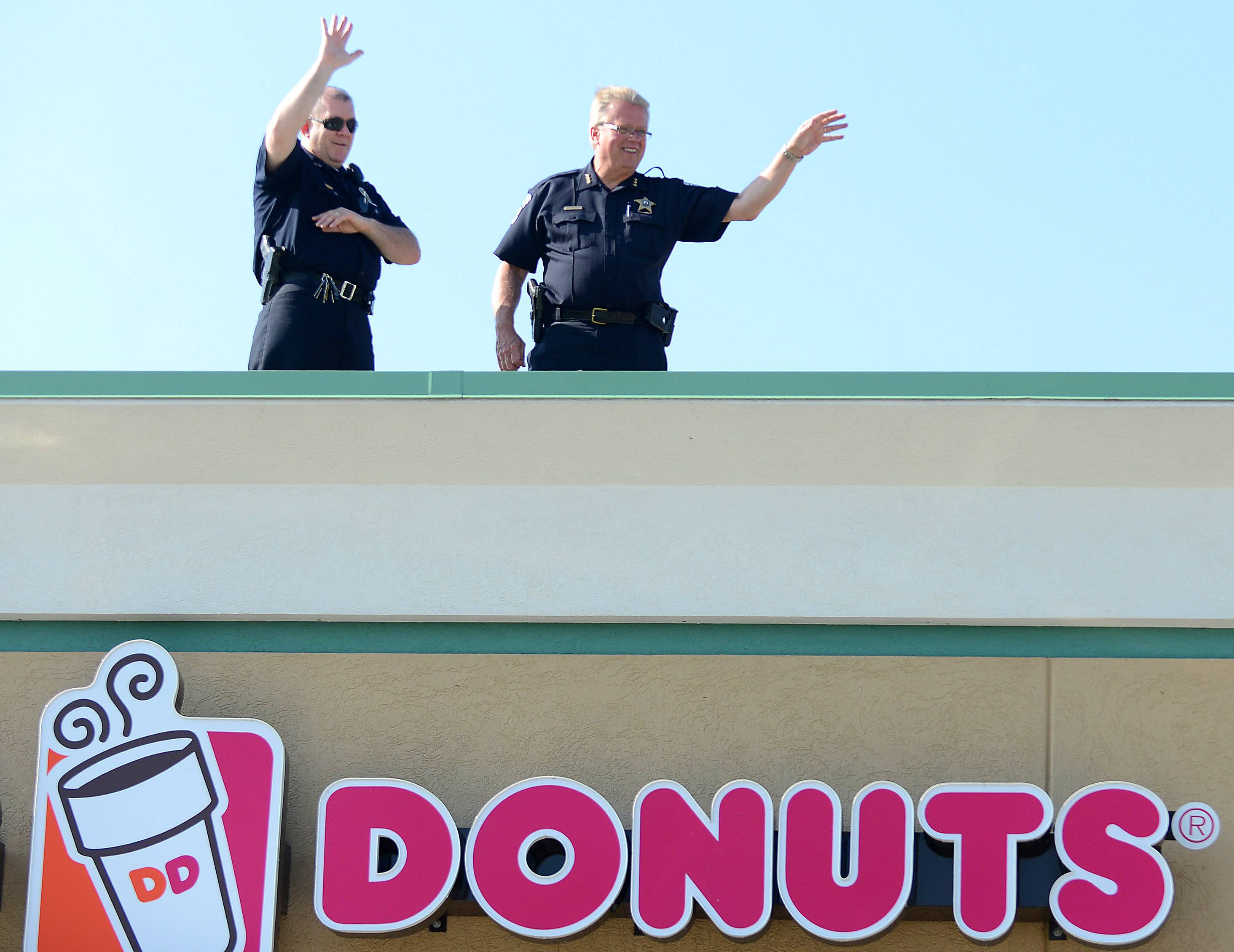 Geneva Police Chief Steve Mexin, left, and Batavia Police Chief Gary Schira wave from tneir spot up high during the Cop on a Rooftop fundraiser at Dunkin Donuts in Batavia Friday morning.