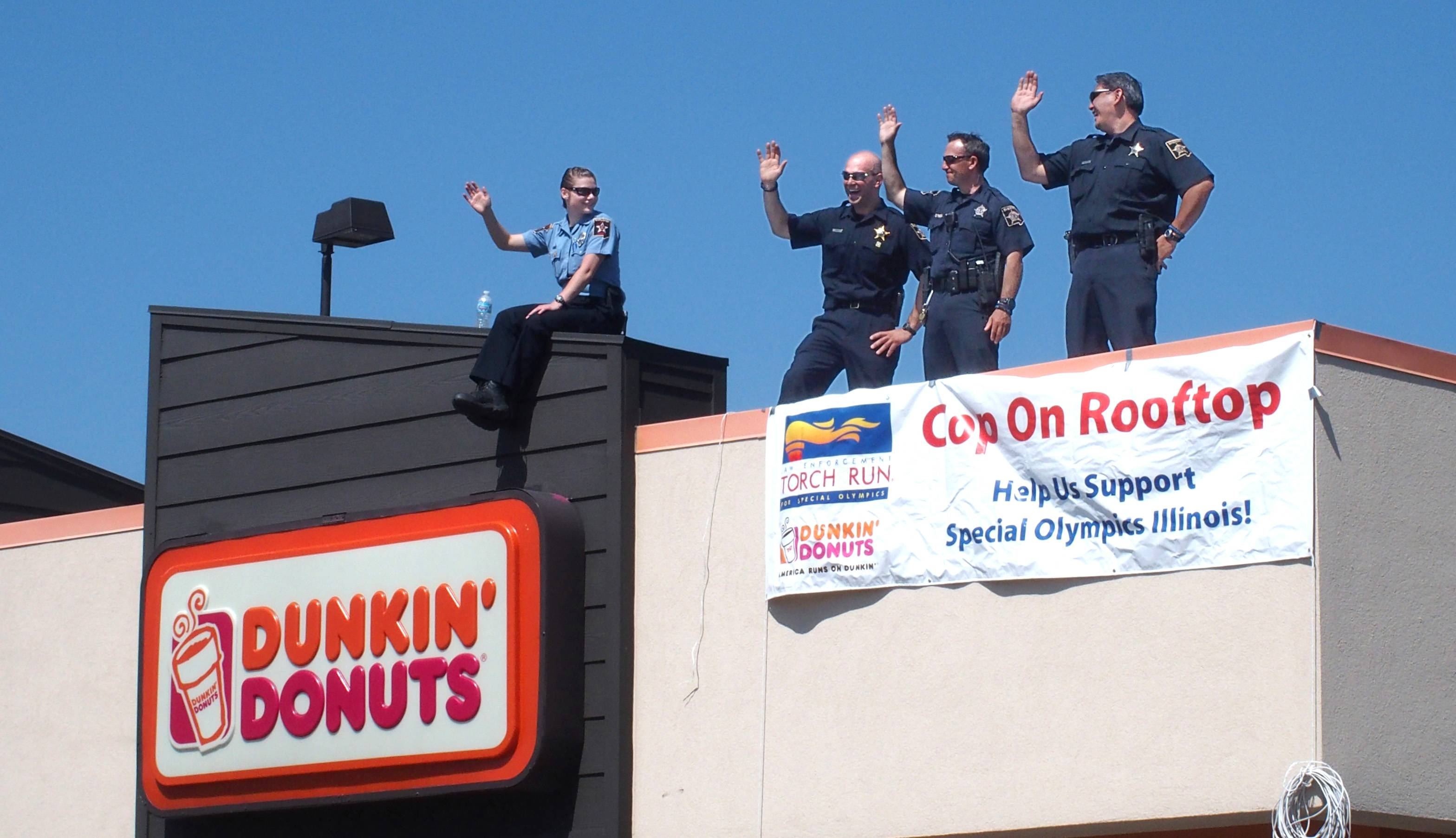 DuPage County sheriff's deputies waved to drivers Friday from the roof of the Dunkin' Donuts at 811 E. Ogden Ave. in Naperville. Cops throughout the state climbed atop 174 doughnut shops during the 12th annual Cop on a Rooftop fundraiser for the Law Enforcement Torch Run for Special Olympics Illinois.