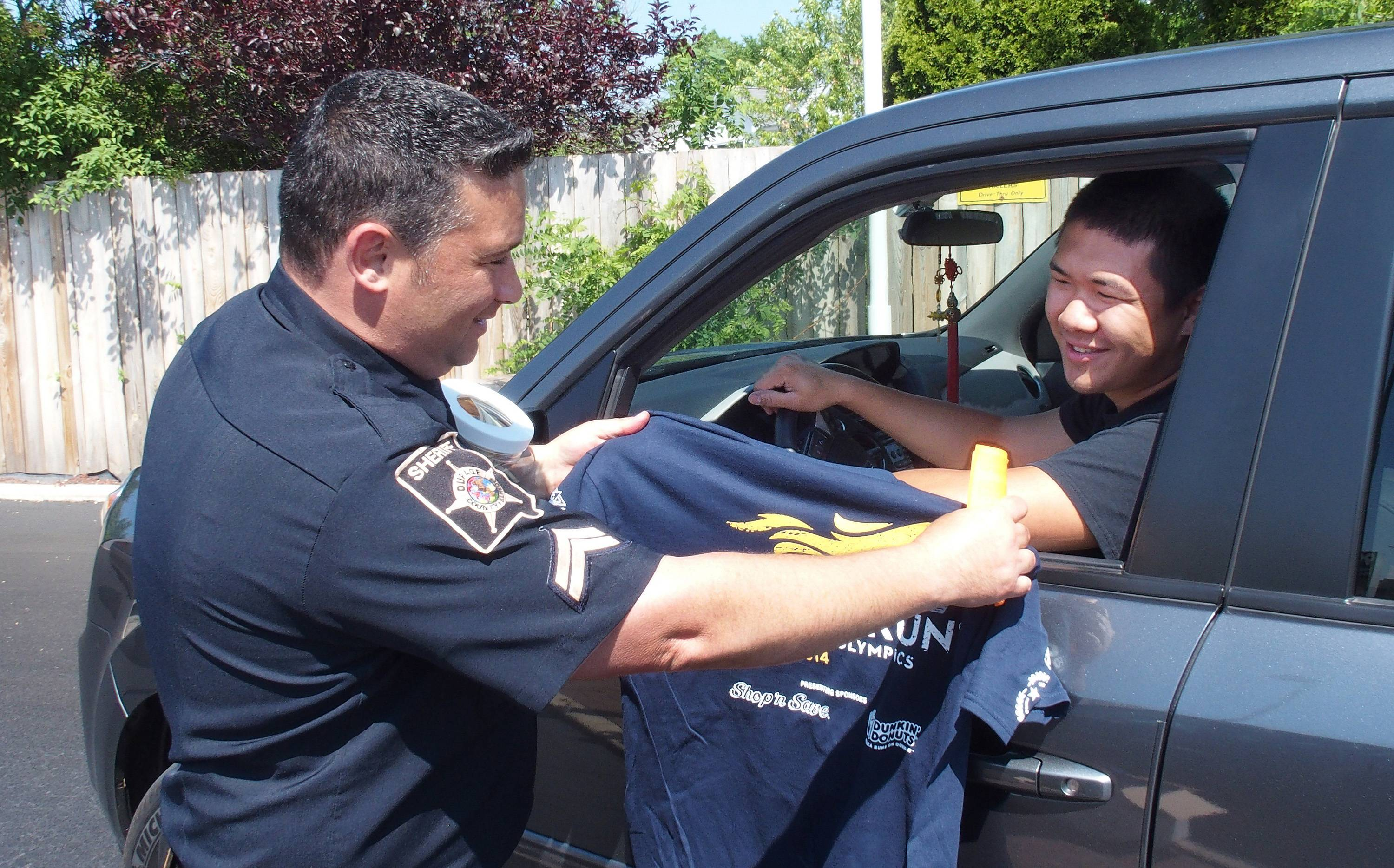 DuPage County sheriff's Cpl. Michael Urso hands a Law Enforcement Torch Run T-shirt to Tony Liu, a participant in the sheriff's Explorers program, who made a donation Friday to Special Olympics Illinois during the Cop on a Rooftop fundraiser at a Dunkin' Donuts in Naperville.