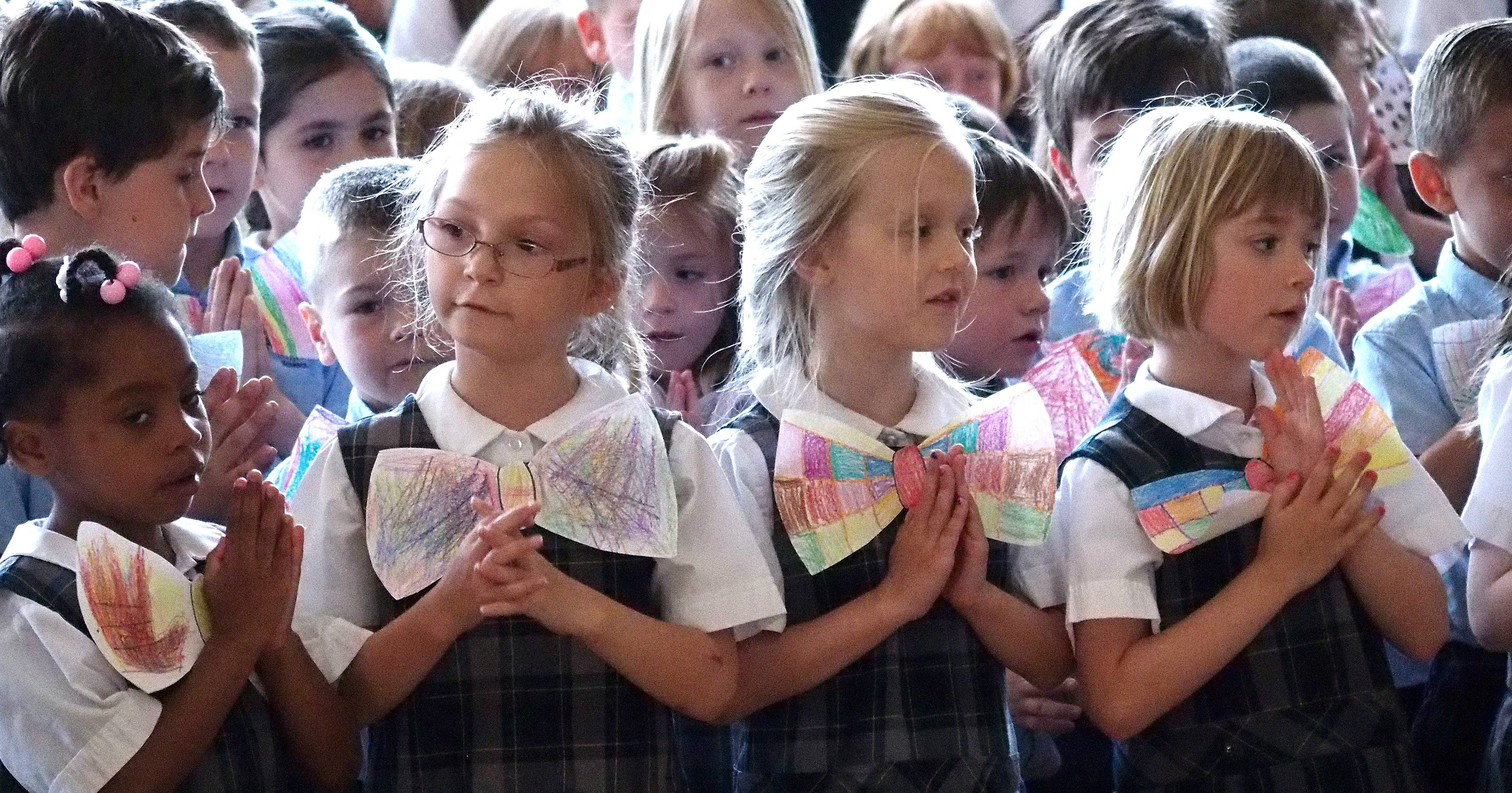 Wearing handmade paper bow ties, kindergartners sing the Hail Mary prayer during an assembly Friday honoring retiring Ss. Peter and Paul Principal Frank Glowaty at the school in Naperville.