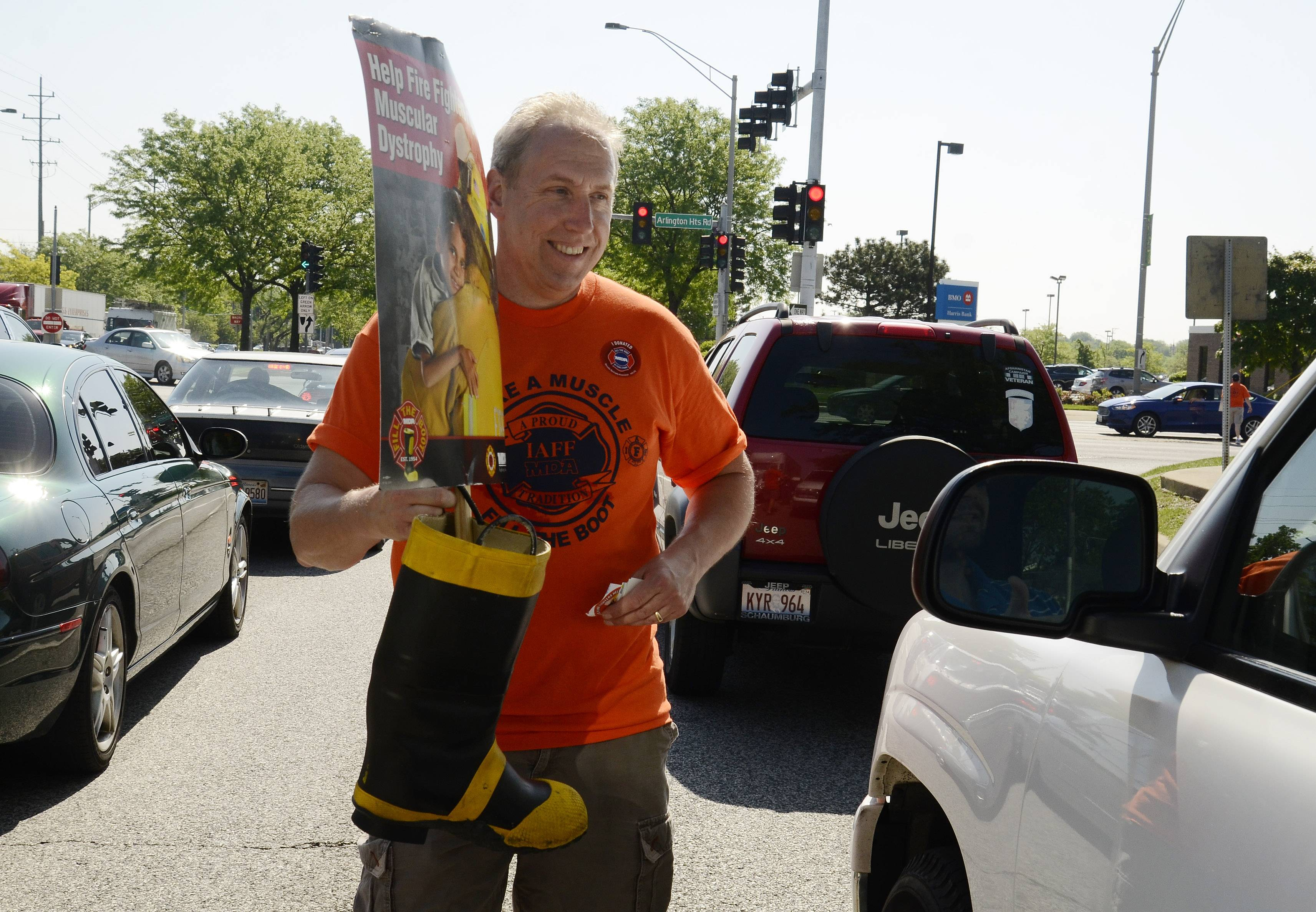 Bill Yowell works the intersection of Palatine Road and Arlington Heights Roads during the Arlington Heights firefighters Fill the Boot campaign Friday.
