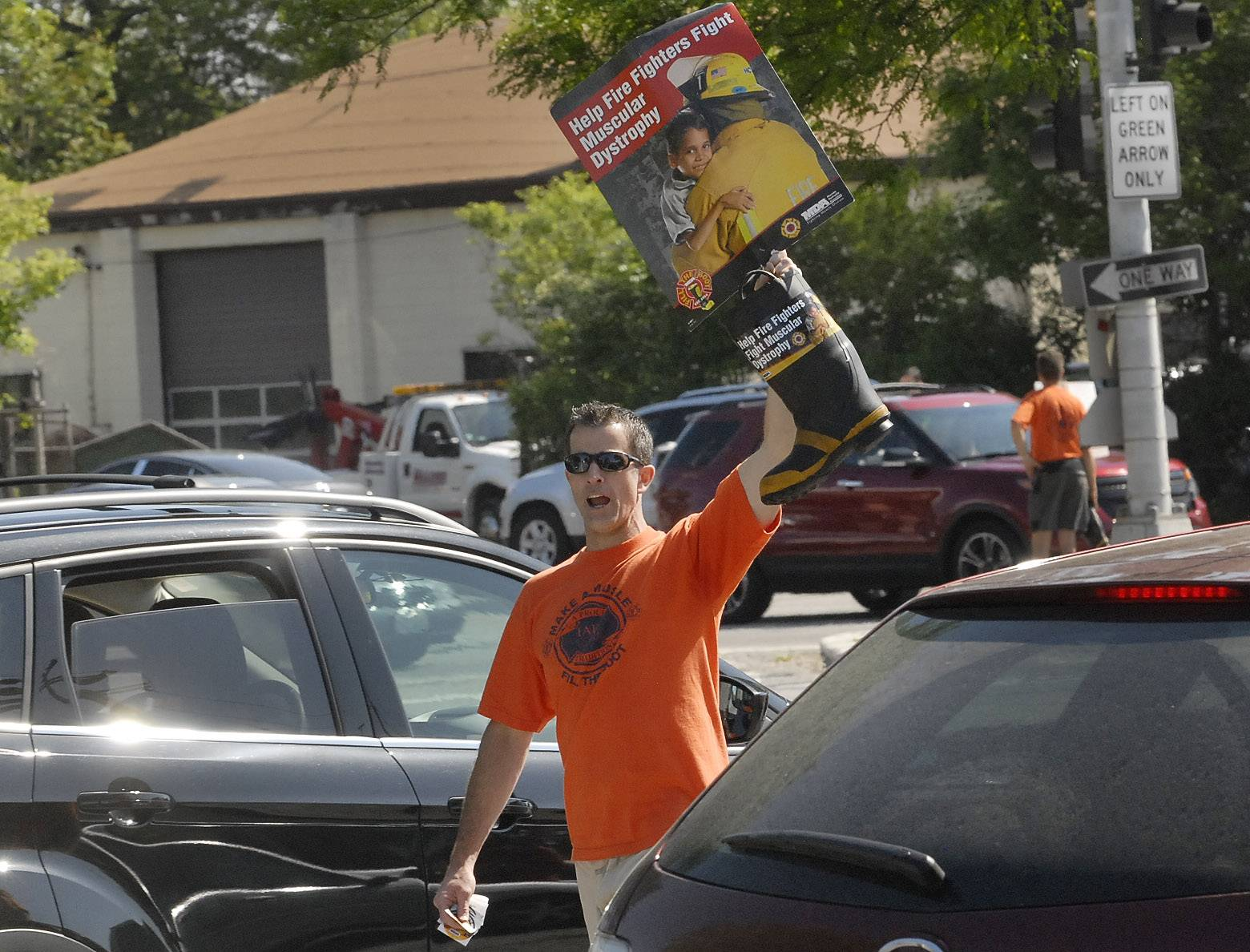 Ted Peterson works the intersection of Palatine Road and Arlington Heights Roads Friday during the Arlington Heights firefighters Fill the Boot campaign.