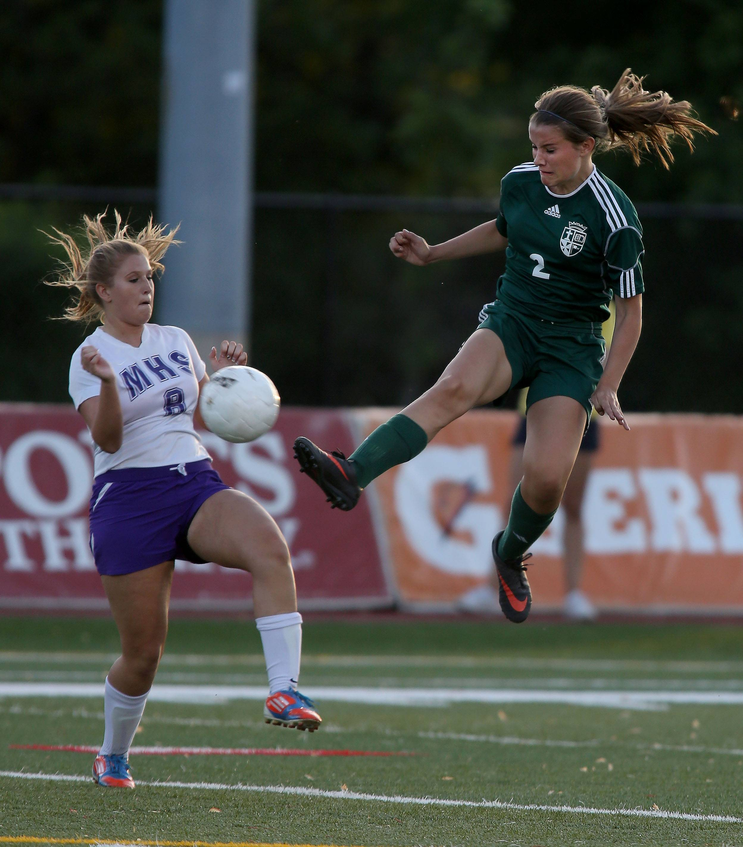 St. Edward's Kathleen Duffy, right, kicks the ball from Amber Olshefski of Manteno during the Class 1A state soccer semifinals at North Central College in Naperville on Friday.