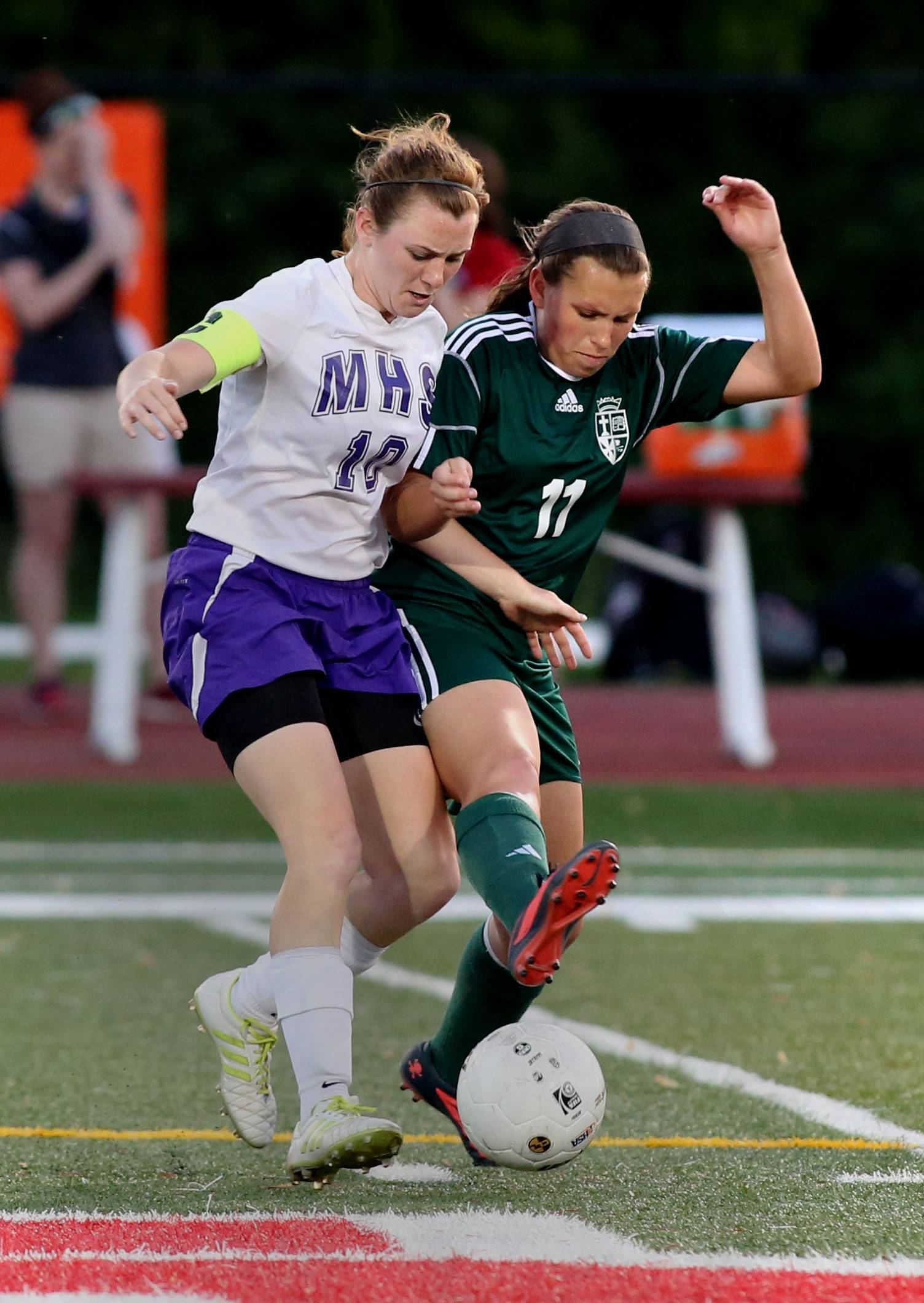St. Edward's Allison Kruk, right, gets a foot on the ball in action against Hannah Ondrey of Manteno, left, during the Class 1A state soccer semifinals at North Central College in Naperville on Friday.