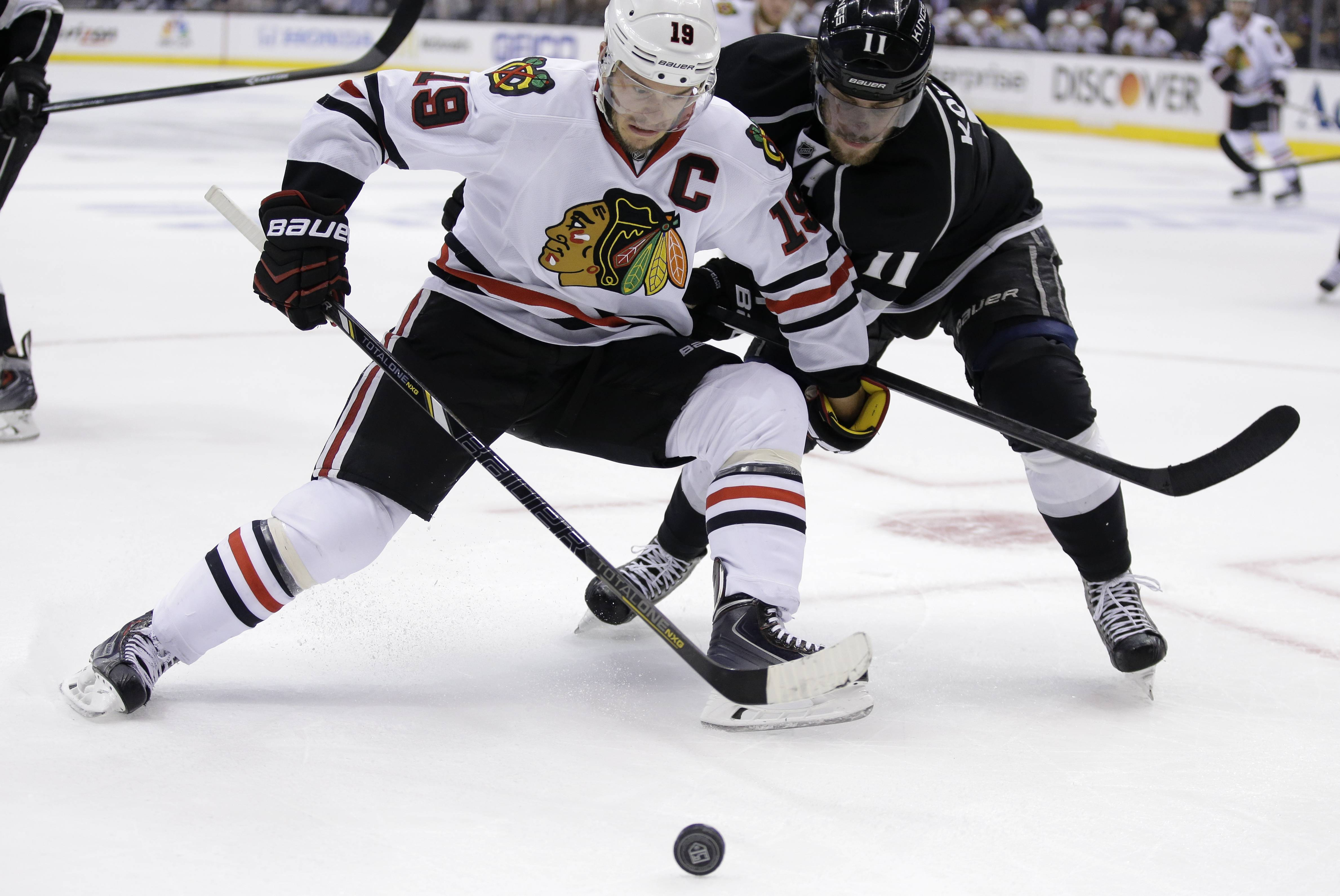 Blackhawks captain Jonathan Toews, left, battles Kings center Anze Kopitar for the puck during Friday night's Game 6 of the Western Conference finals in Los Angeles.