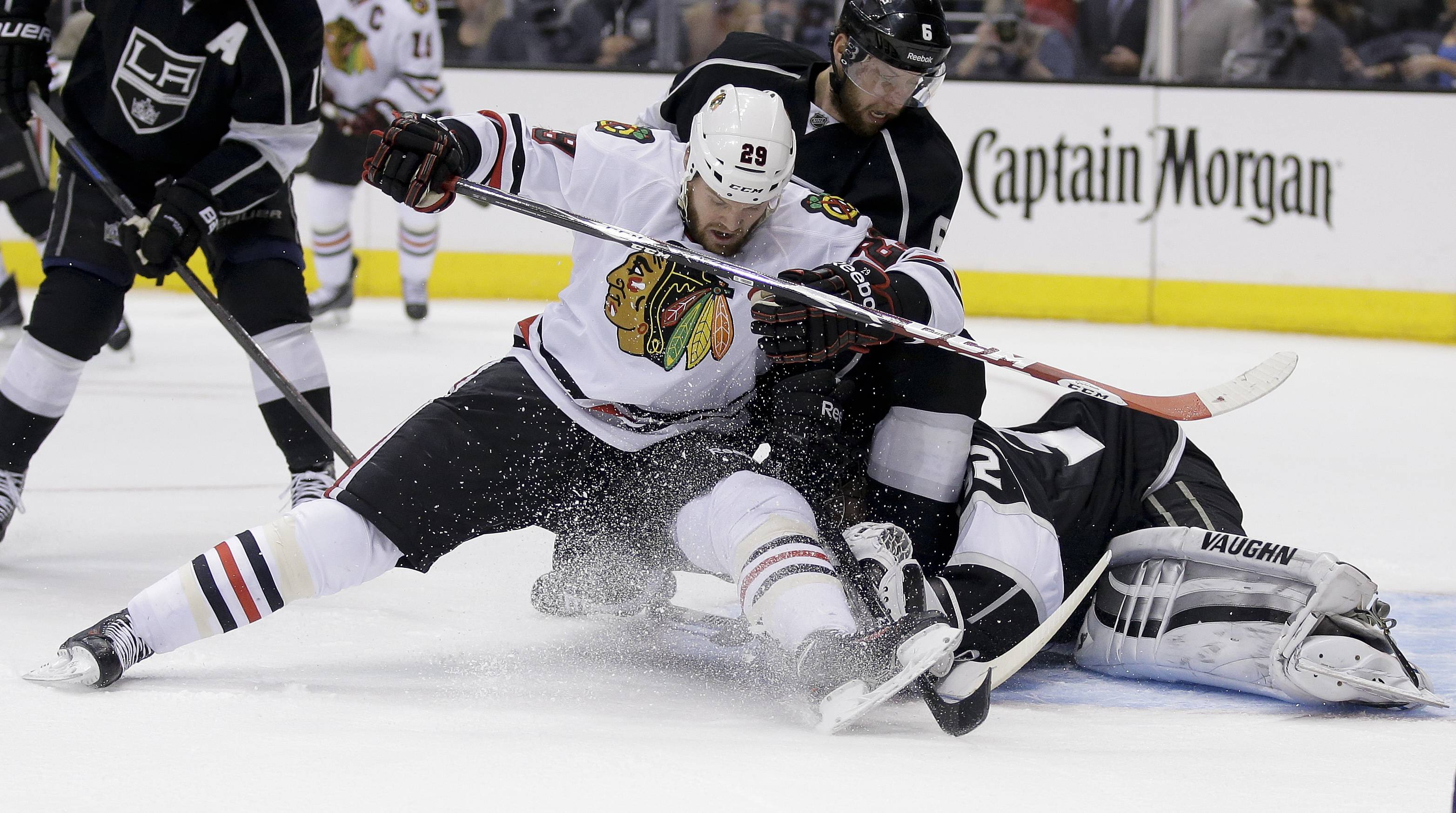Los Angeles Kings goalie Jonathan Quick, right, blocks a shot by Chicago Blackhawks left wing Bryan Bickell as Kings' Jake Muzzin helps defend during first period.