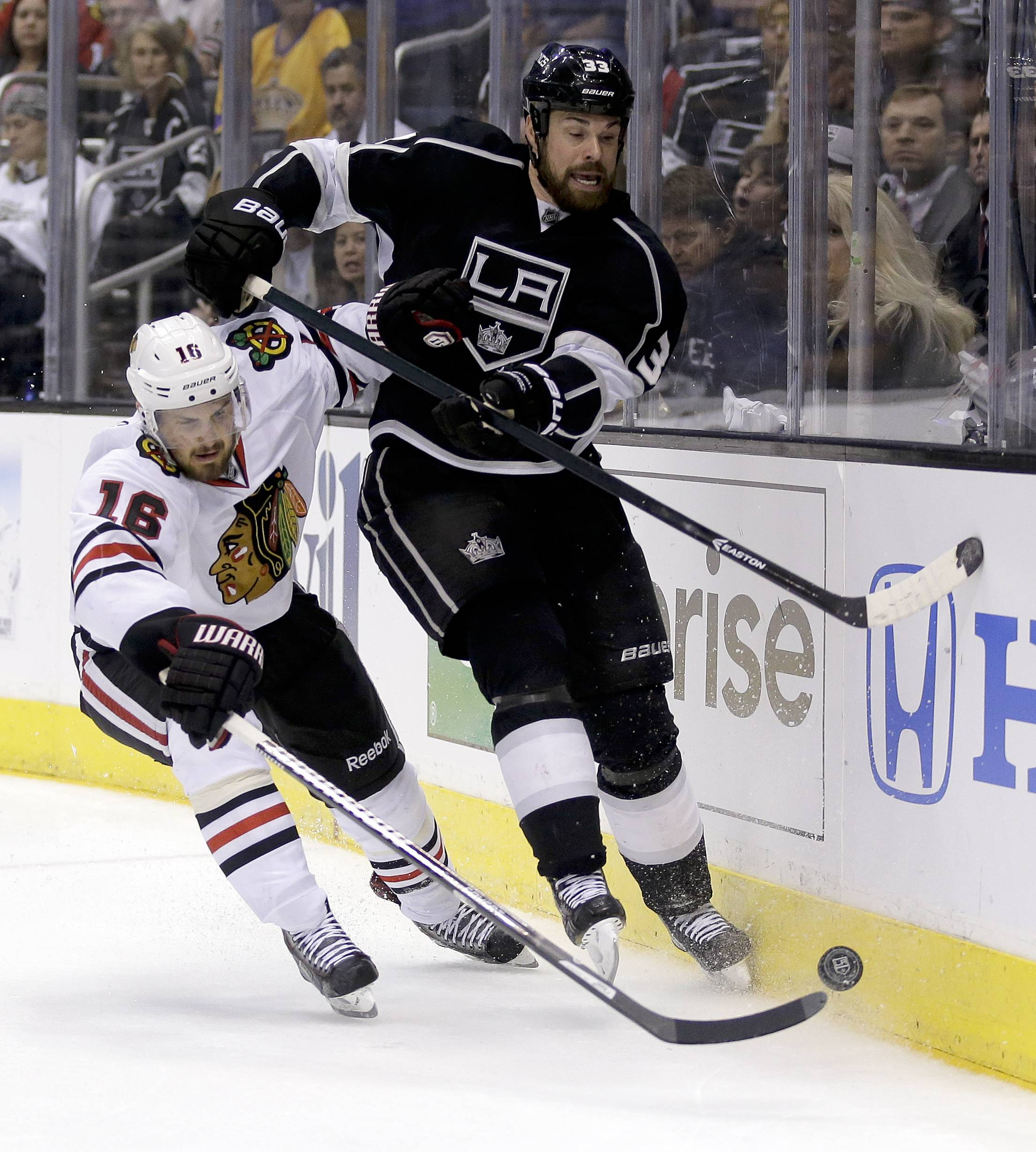Chicago Blackhawks center Marcus Kruger, left, battles Los Angeles Kings defenseman Willie Mitchell for the puck during  the third period .
