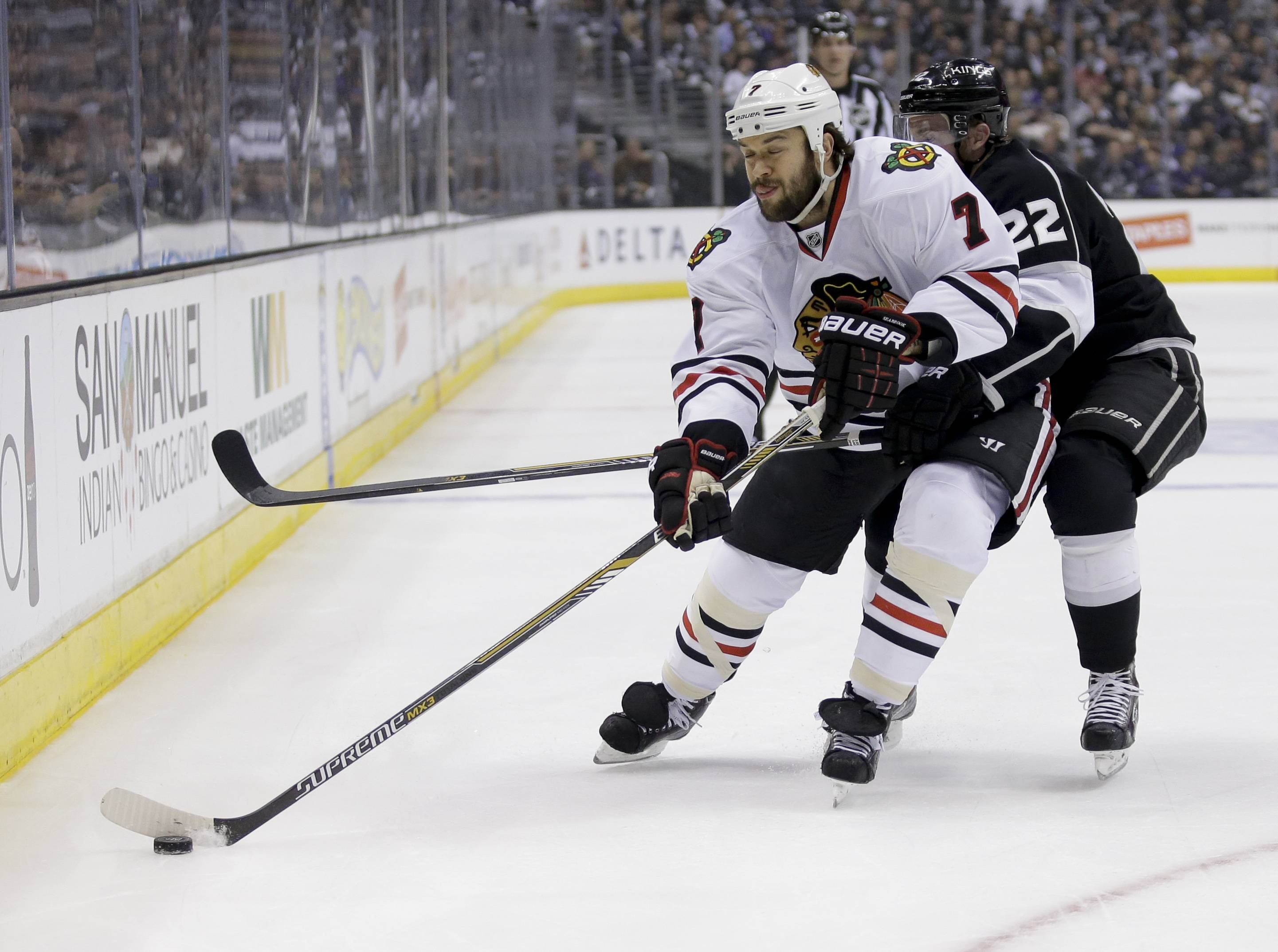 Chicago Blackhawks defenseman Brent Seabrook, left, competes against Los Angeles Kings center Trevor Lewis for the puck during the first period.