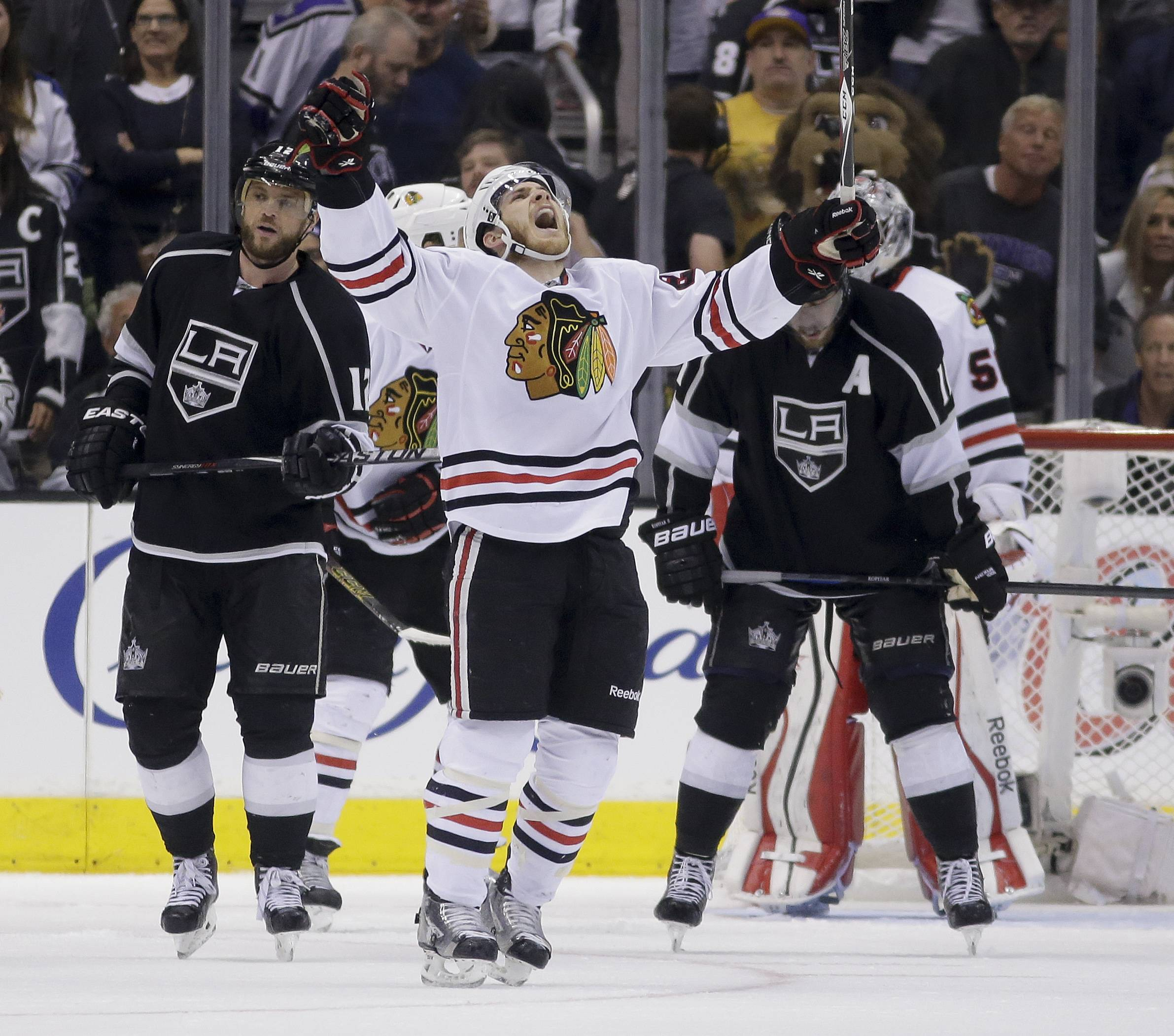 Chicago Blackhawks right wing Ben Smith, middle, celebrates as Los Angeles Kings right wing Marian Gaborik, left, and center Anze Kopitar look away after the game.