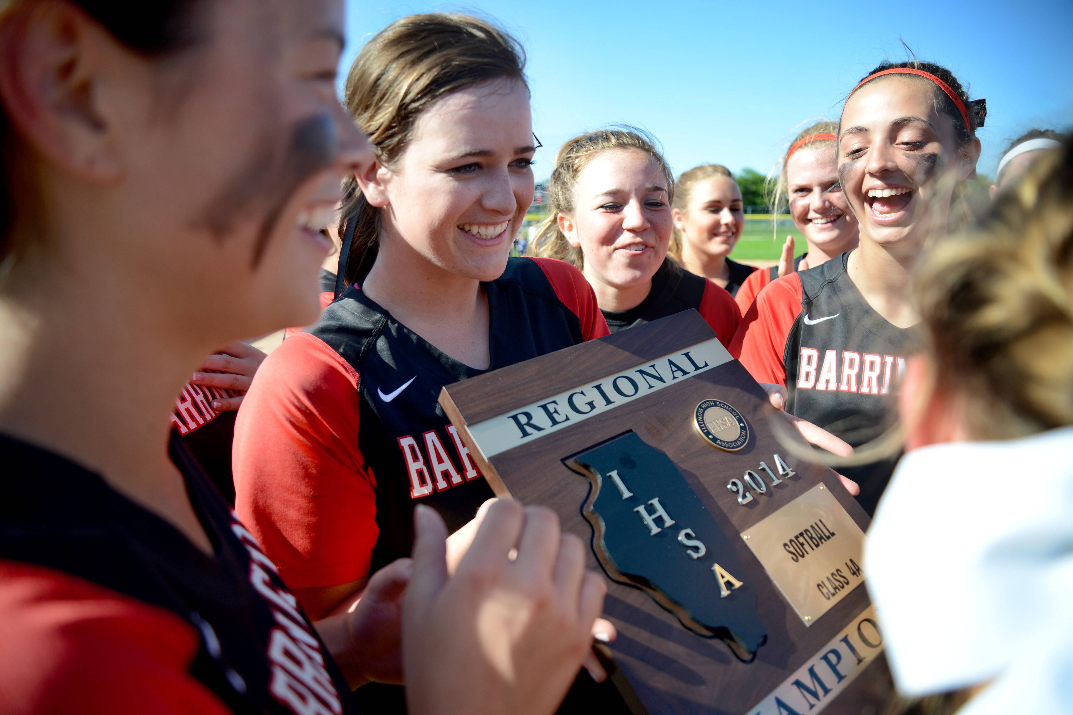 Barrington's Carly Kordich holds the team's Class 4A girls softball regional championship plaque as teammates gather around after their 10-0 win over Cary-Grove on Friday, May 30.