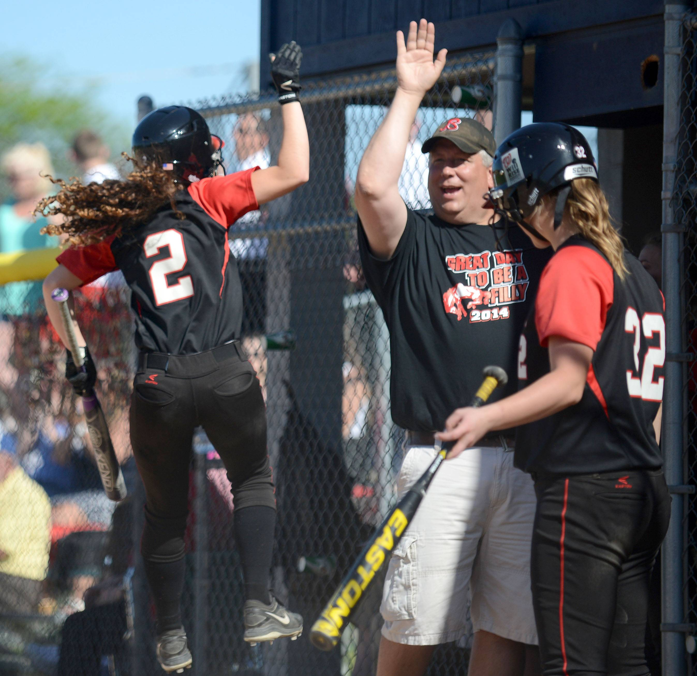 Barrington's Jenna Privatsky (2) leaps into the air to give assistant coach Jon Sander a high-five after scoring a run over Cary-Grove in the second inning of the Class 4A girls softball regional championship in Cary on Friday, May 30.