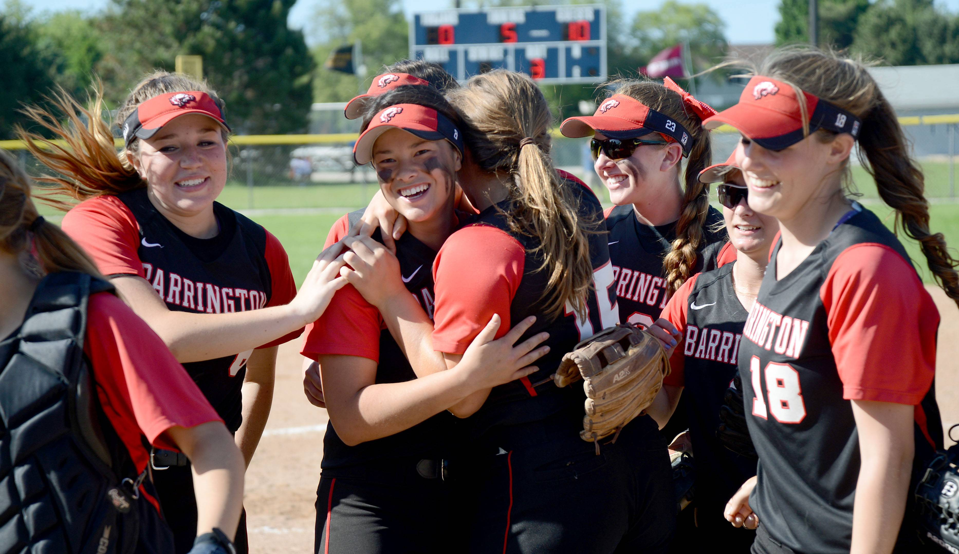 Barrington's Keenan Dolezal, center, facing, is hugged by teammate Rachel MacDonald (15) and others after their 10-0 win over Cary-Grove in the Class 4A girls softball regional championship in Cary on Friday, May 30.