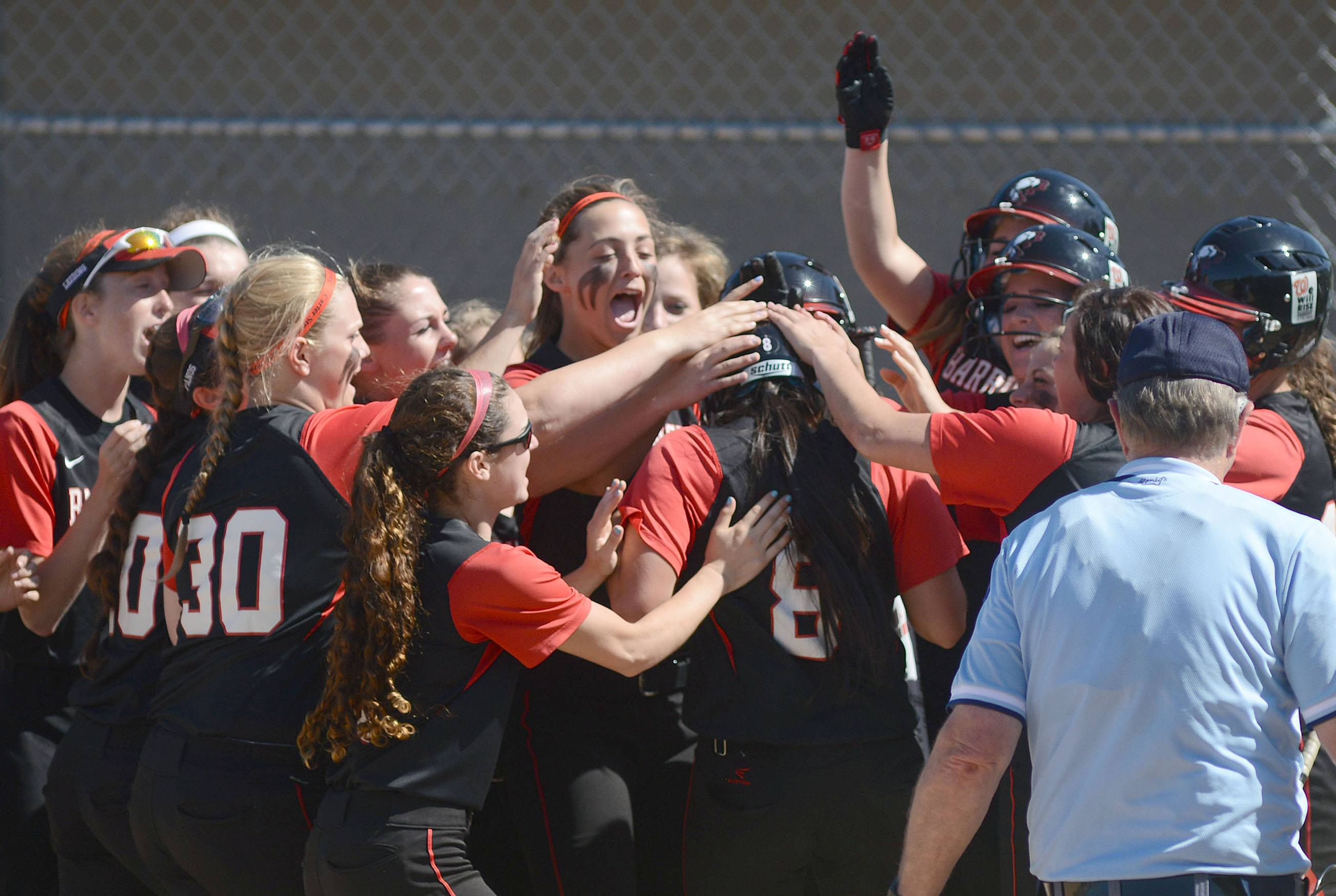 Barrington's Jennifer Inamoto (8) is swarmed by teammates at home plate after her home run in the first inning vs. Cary-Grove in the Class 4A girls softball regional championship in Cary on Friday, May 30.