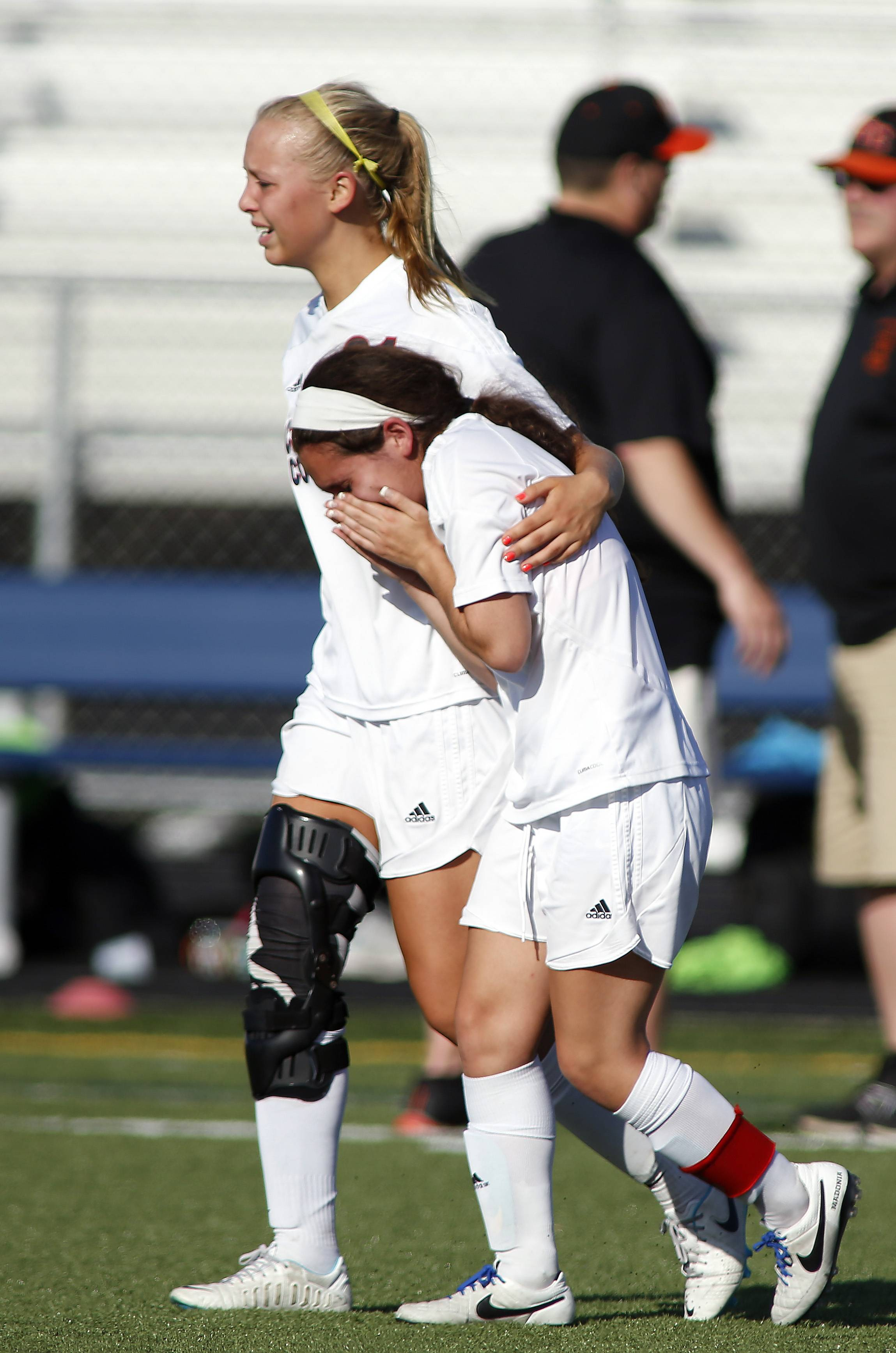 Conant's Katie Lomas (21) consoles teammate Bianca Madonia after the Cougars' loss to St. Charles East on Friday at Conant.