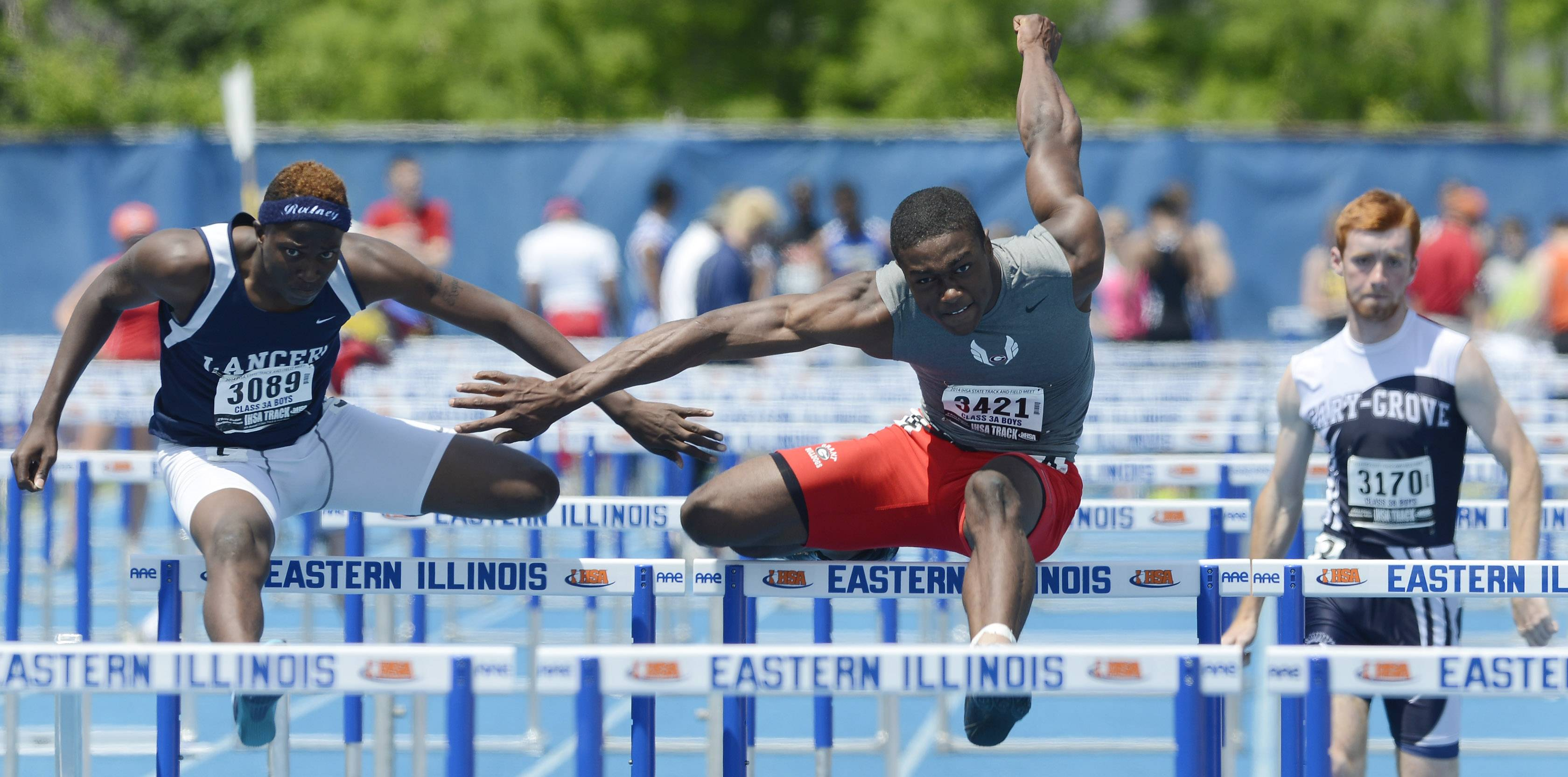 Grant's Jonathan Wells, middle, runs between Belleville East's William Session, left, and Cary-Grove's Michael Saxon in the 110-meter high hurdles during the boys Class 3A state track and field preliminaries in Charleston Friday.