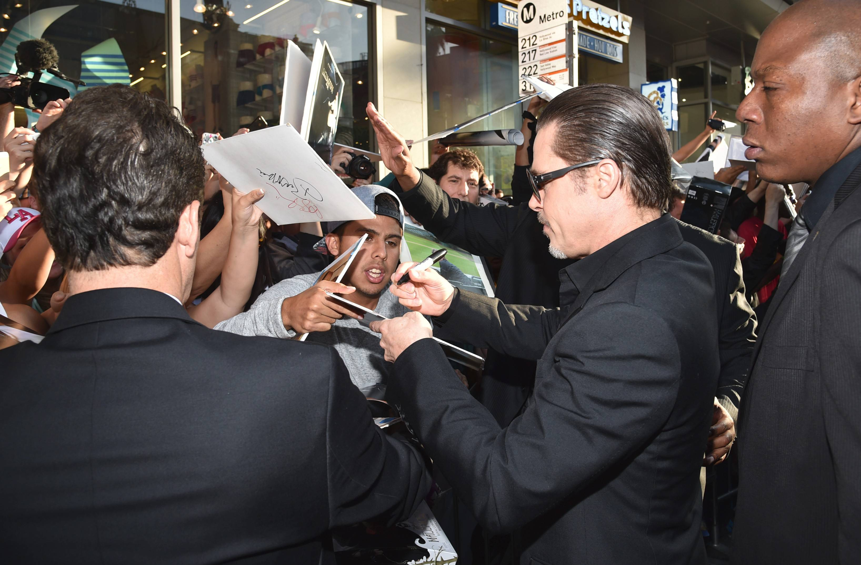"Brad Pitt signs autographs at the world premiere of ""Maleficent"" at the El Capitan Theatre on Wednesday in Los Angeles."