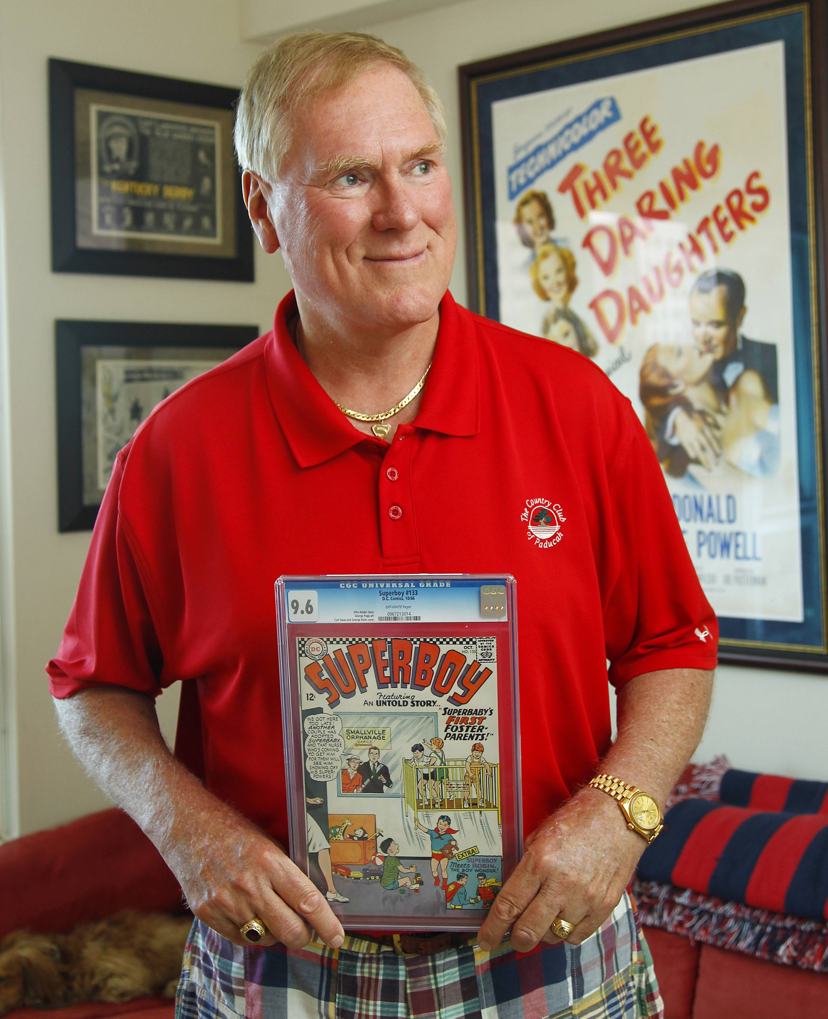 John C. Wise, poses in his San Diego home with a 1966 Super Boy comic.