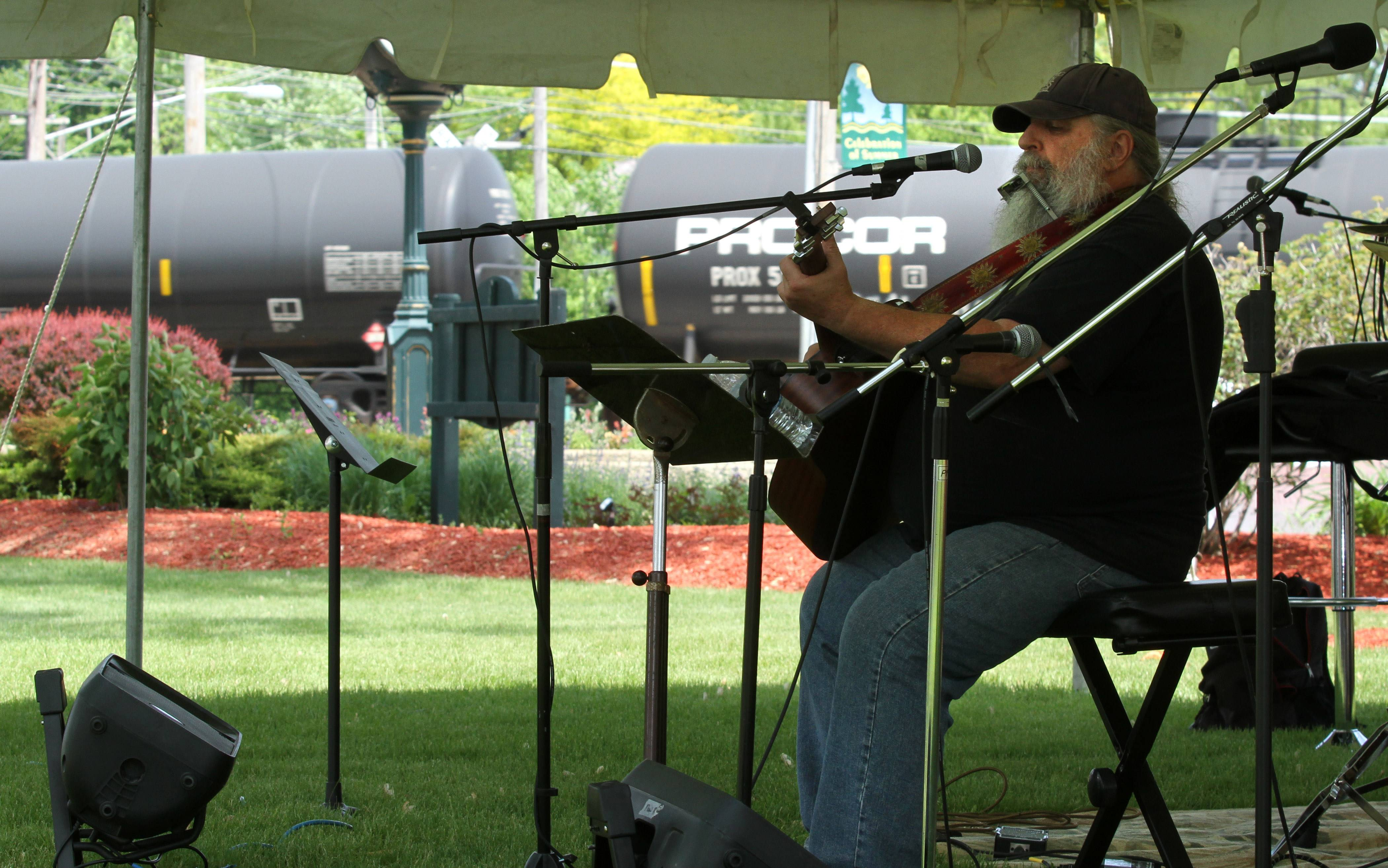 Jimmy Liggett, a Northbrook carpenter by trade, continued to perform solo Saturday as a loud cargo train traveled past Lehmann Park during Lake Villa's Art in the Park art and music festival