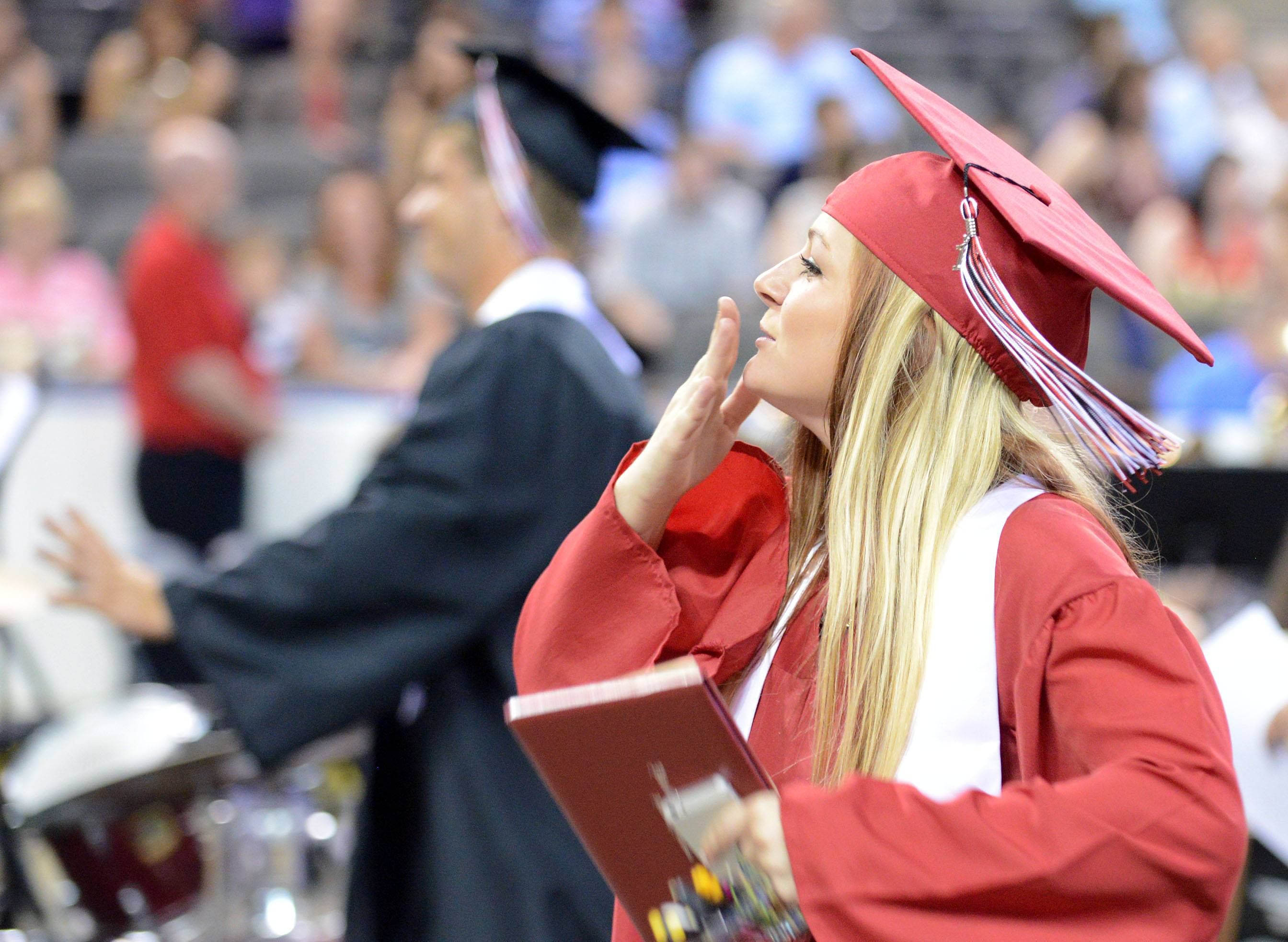 Emily Seymour blows kisses to her family in the stands as she exits the floor of Huntley High School's commencement ceremony at the Sears Centre in Hoffman Estates on Saturday, May 31.