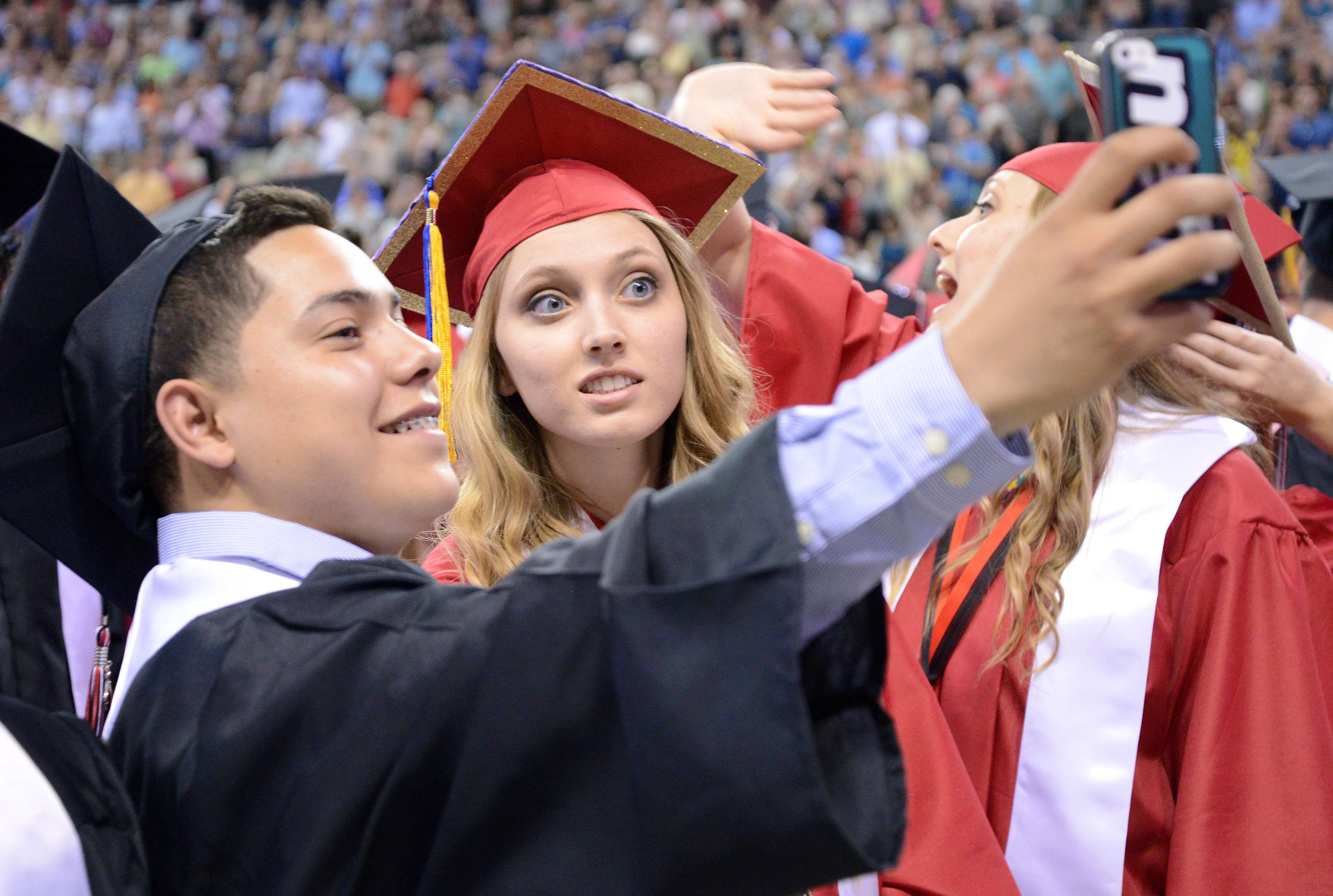 Alan Beltran and Rachel Bednarczyk take a selfie as they are pronounced graduates at the end of Huntley High School's commencement ceremony at the Sears Centre in Hoffman Estates on Saturday, May 31.