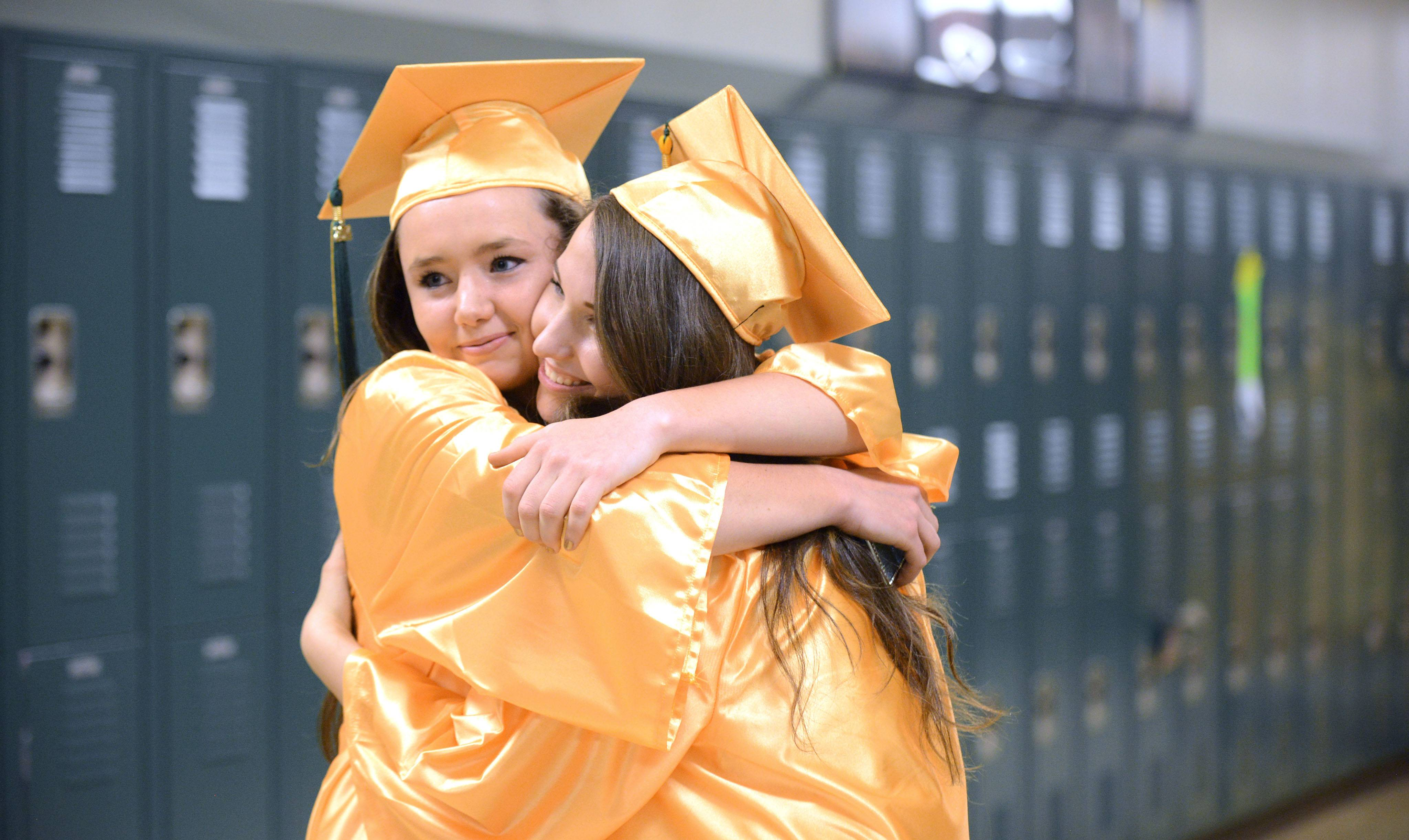 Crystal Lake South graduates Sydney Barnett, left, and Zoe Godsted share a tight hug before going to their assigned classrooms to away their commencement ceremony on the football field on Saturday, May 31.
