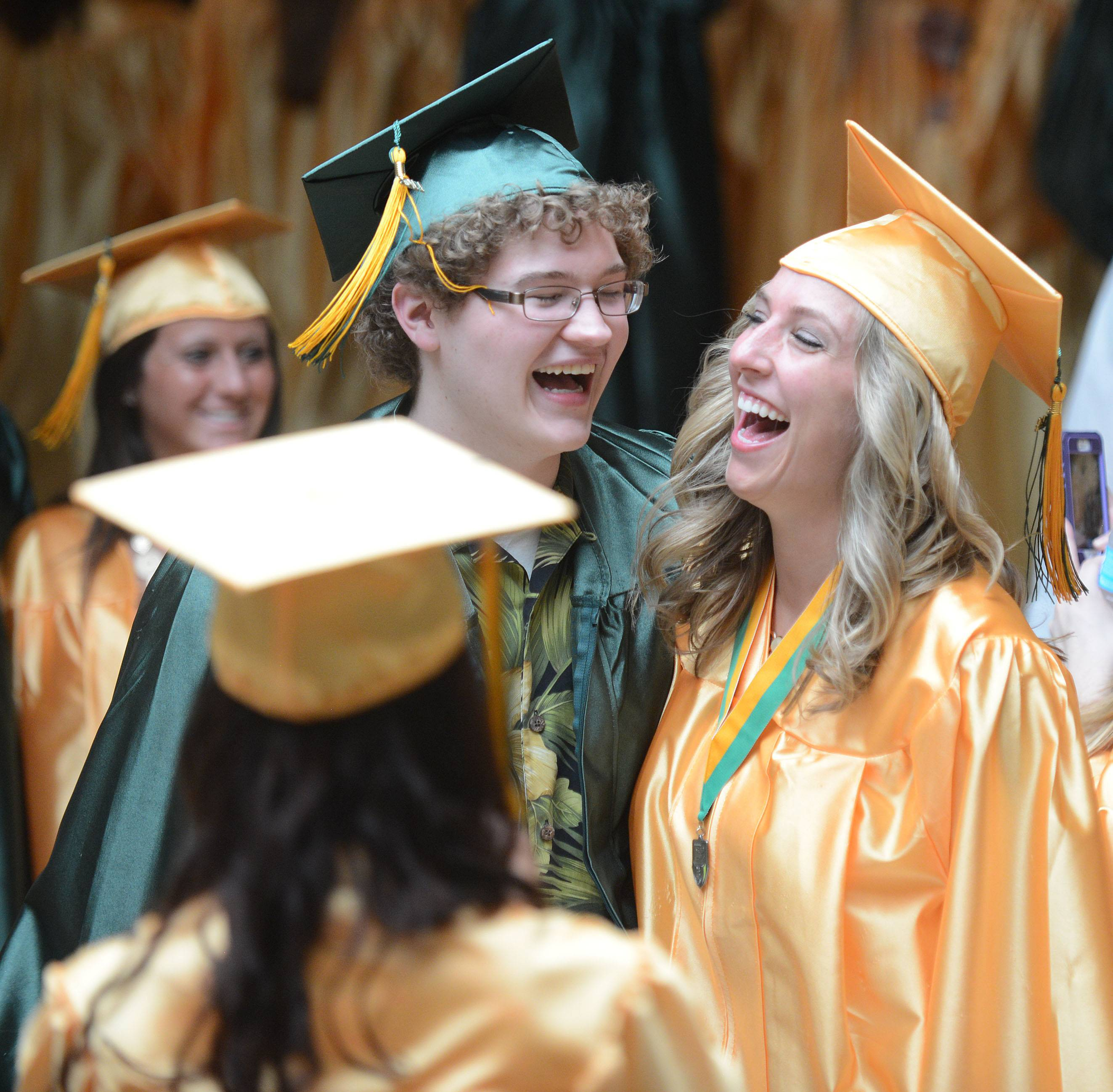 Crystal Lake South graduates Alex LoSchiavo, left, and Holly Schumacher, right, break out into laughter while Ashley Resek takes their picture before their commencement ceremony on Saturday, May 31.