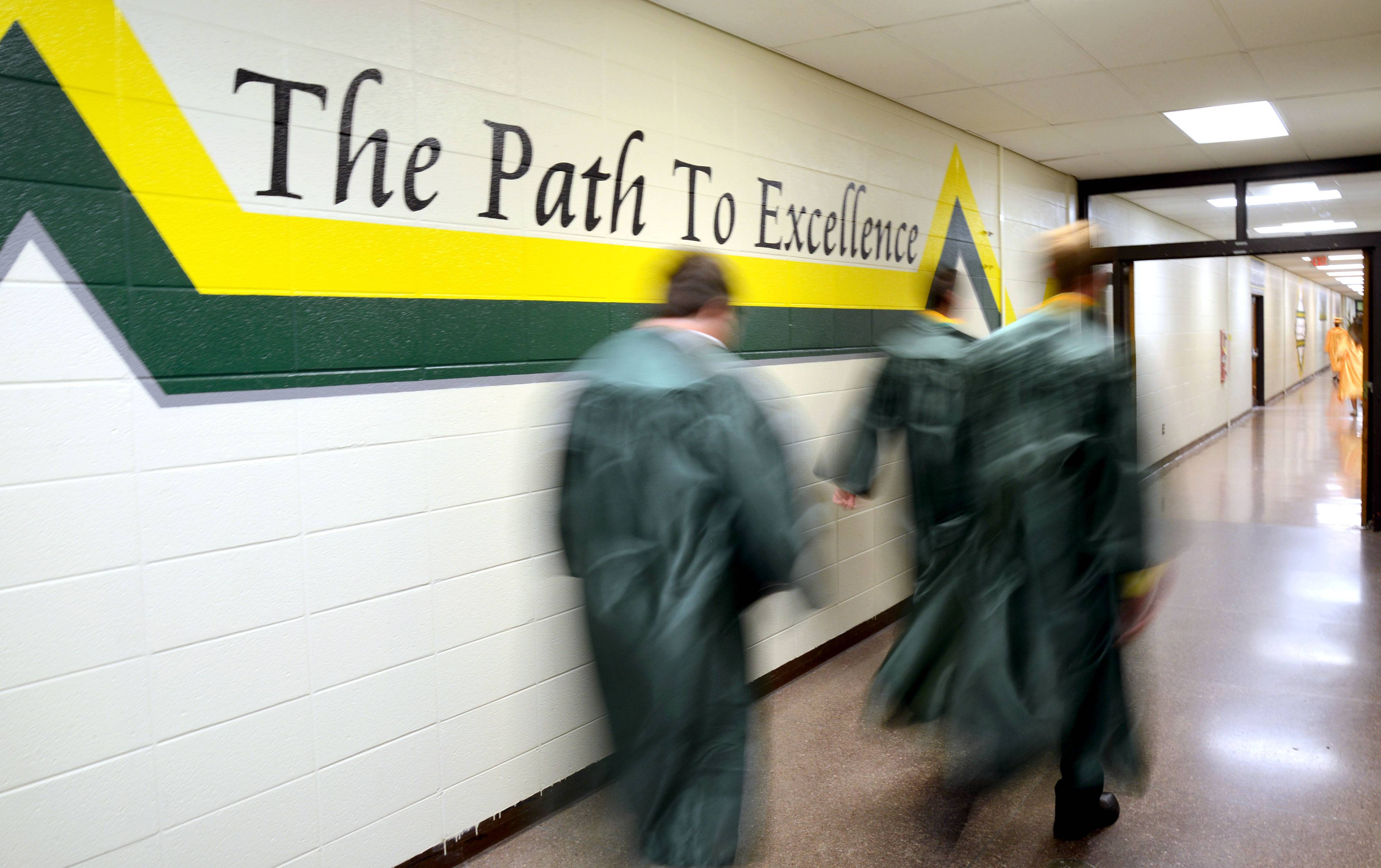 Crystal Lake South graduates file down a hallway to classrooms to await lining up for their commencement ceremony on Saturday, May 31.