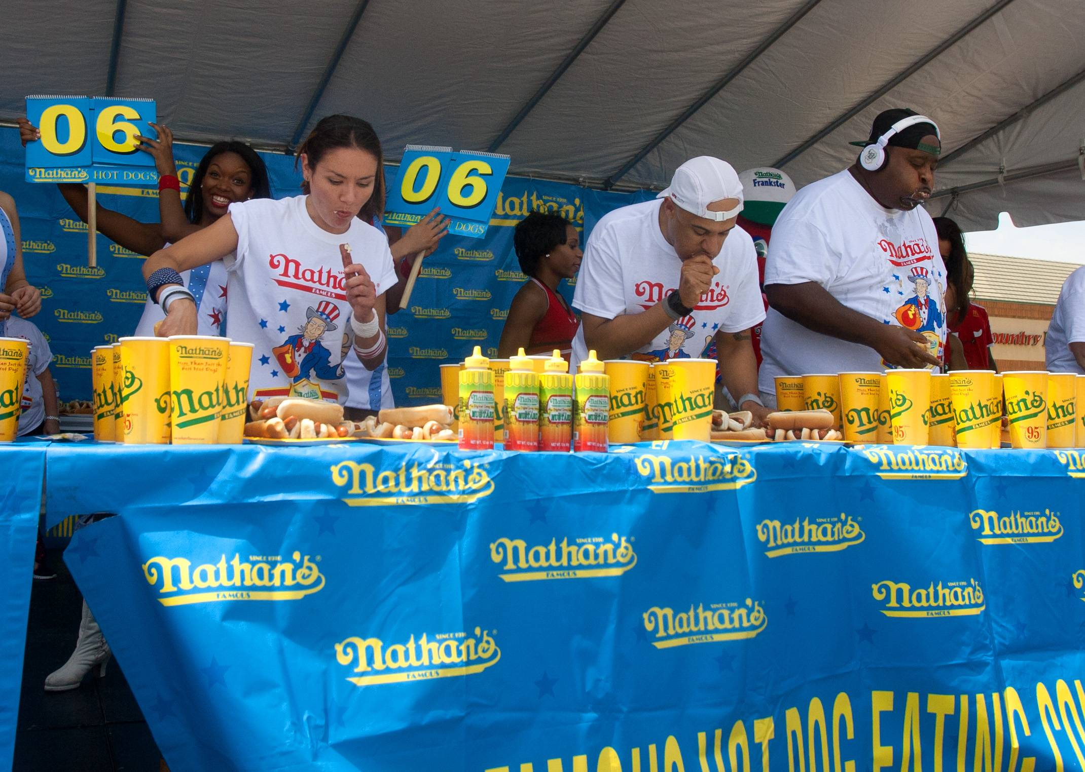 "Michelle Lesco of Tucson, Arizona, left, is en route to a win in a hot dog-eating contest in the Bloomingdale Kmart parking lot. She ate 28½ hot dogs. Third-place finisher Yasir Salem, center, ate 26, while Eric ""Badlands"" Booker, right, ate 27½ hot dogs."