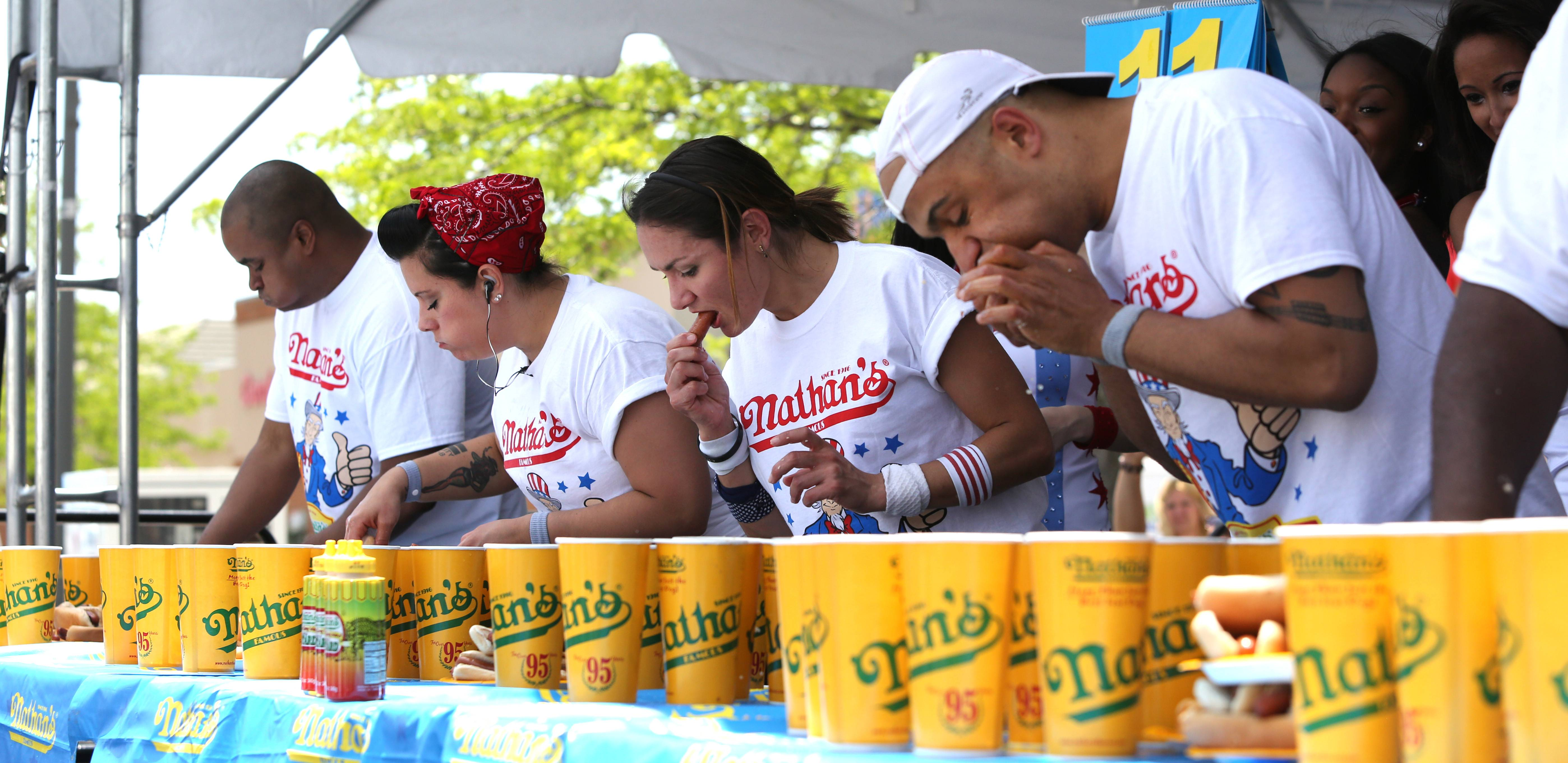 Michelle Lesco of Tucson, Arizona, third from left, is en route to a win during a hot dog-eating contest in the Bloomingdale Kmart parking lot. She ate 28½ hot dogs. Yasir Salem, right, finished third with 26 hot dogs.