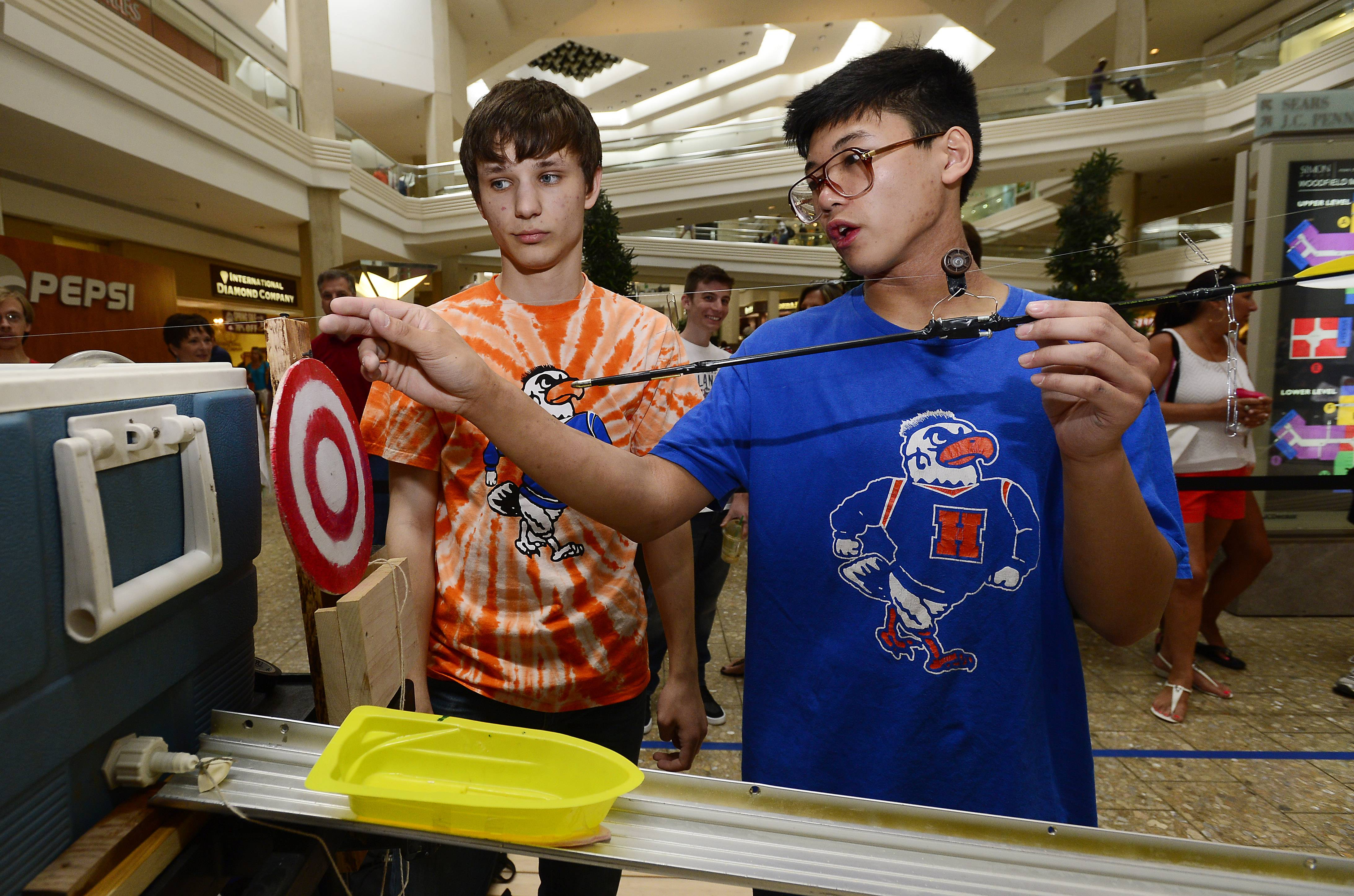 Lars Gavris, 17, of Hoffman Estates High School and recent graduate Gregg Lugo, 18, fine tune their Rube Goldberg machine, which was used to cut the ribbon on the new Boy Scouts recruitment center at Woodfield Mall.