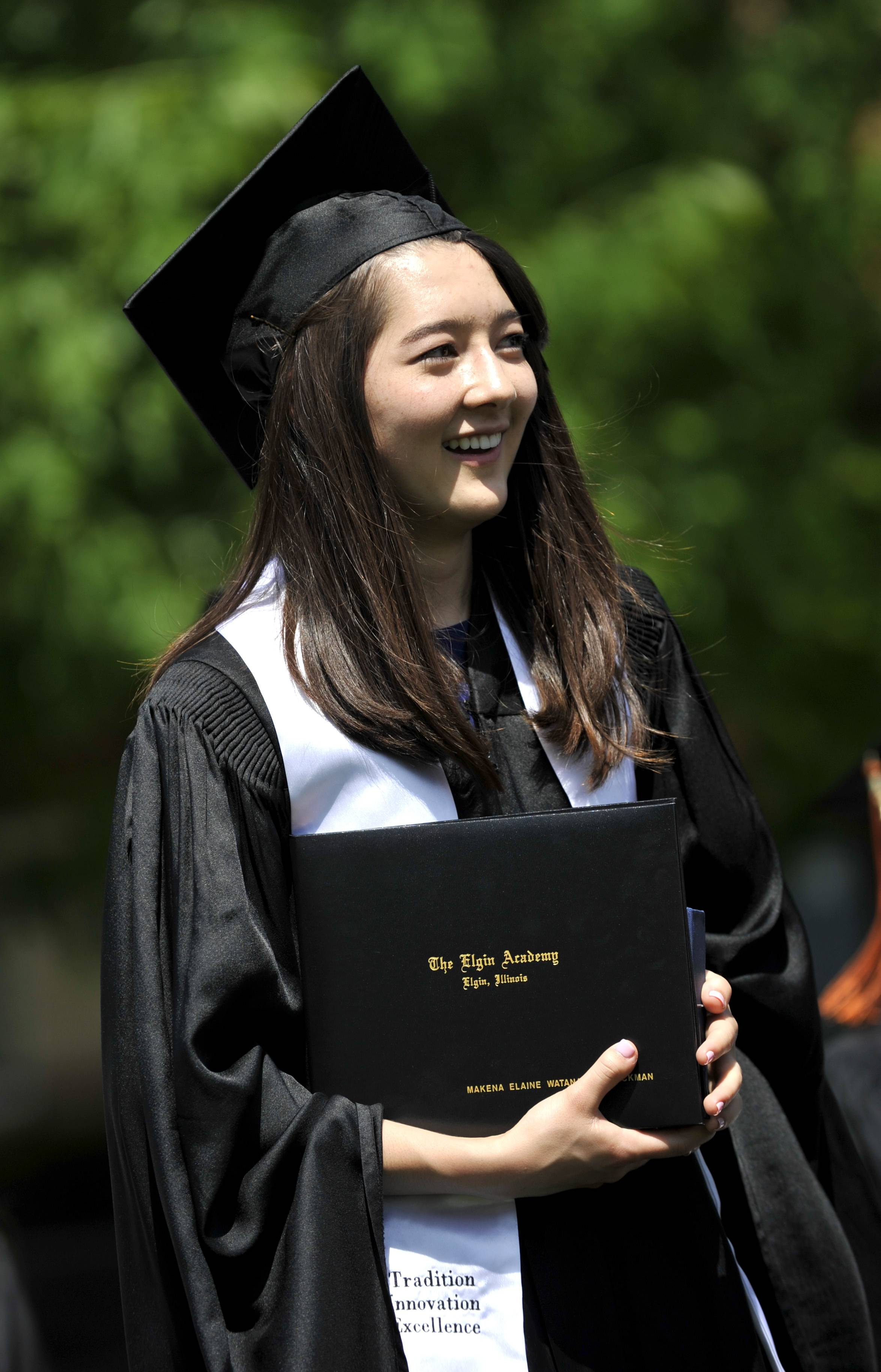 Makena Watanabe Barickman of Geneva smiles at the crowd after receiving her diploma at the Elgin Academy commencement on Saturday, May 30.