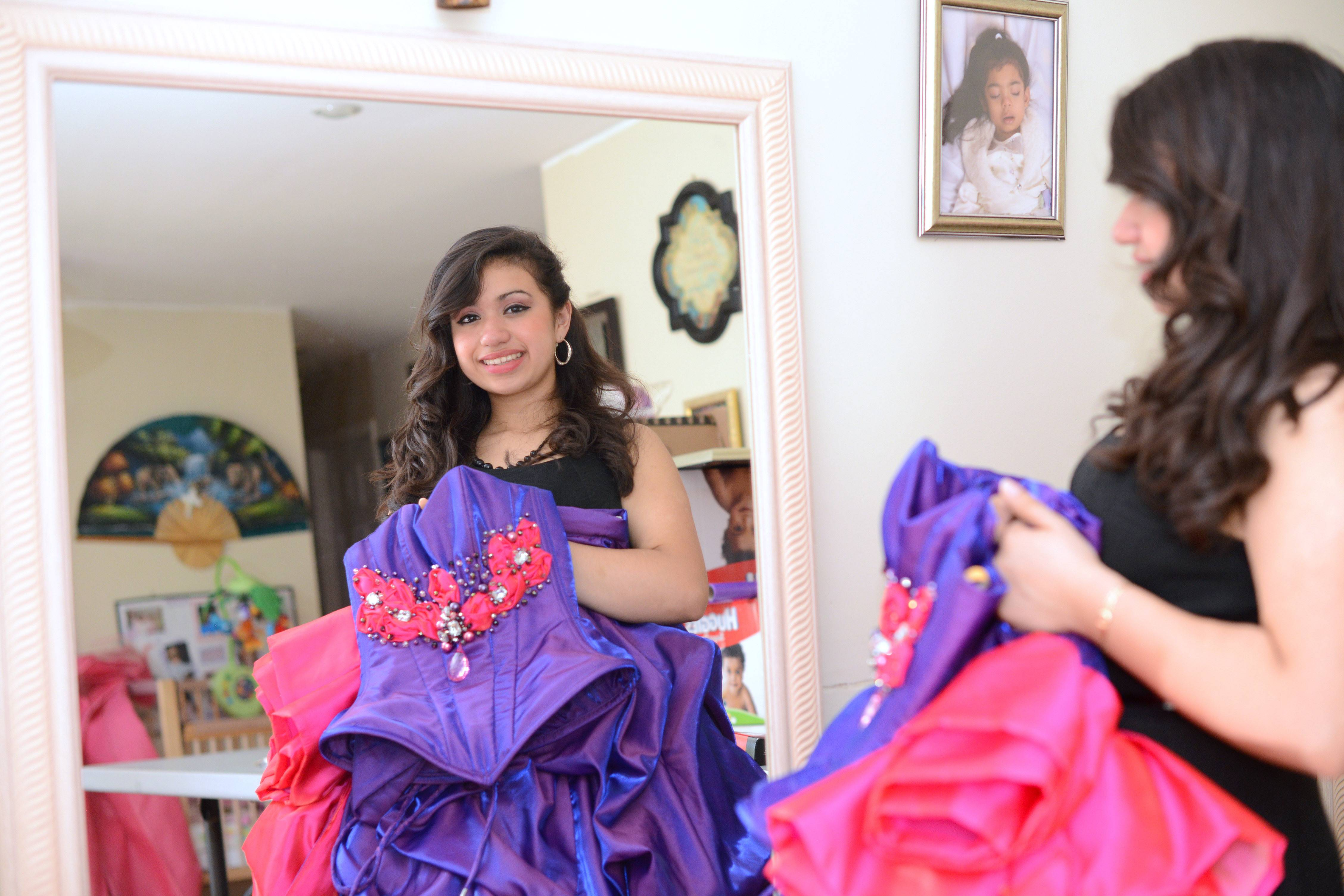 Bianca Huerta, 15, of Carpentersville shows the quinceañera dress that her mother, Brandy, won for her through a Facebook contest. It's one of many prizes her mother won for her daughter.