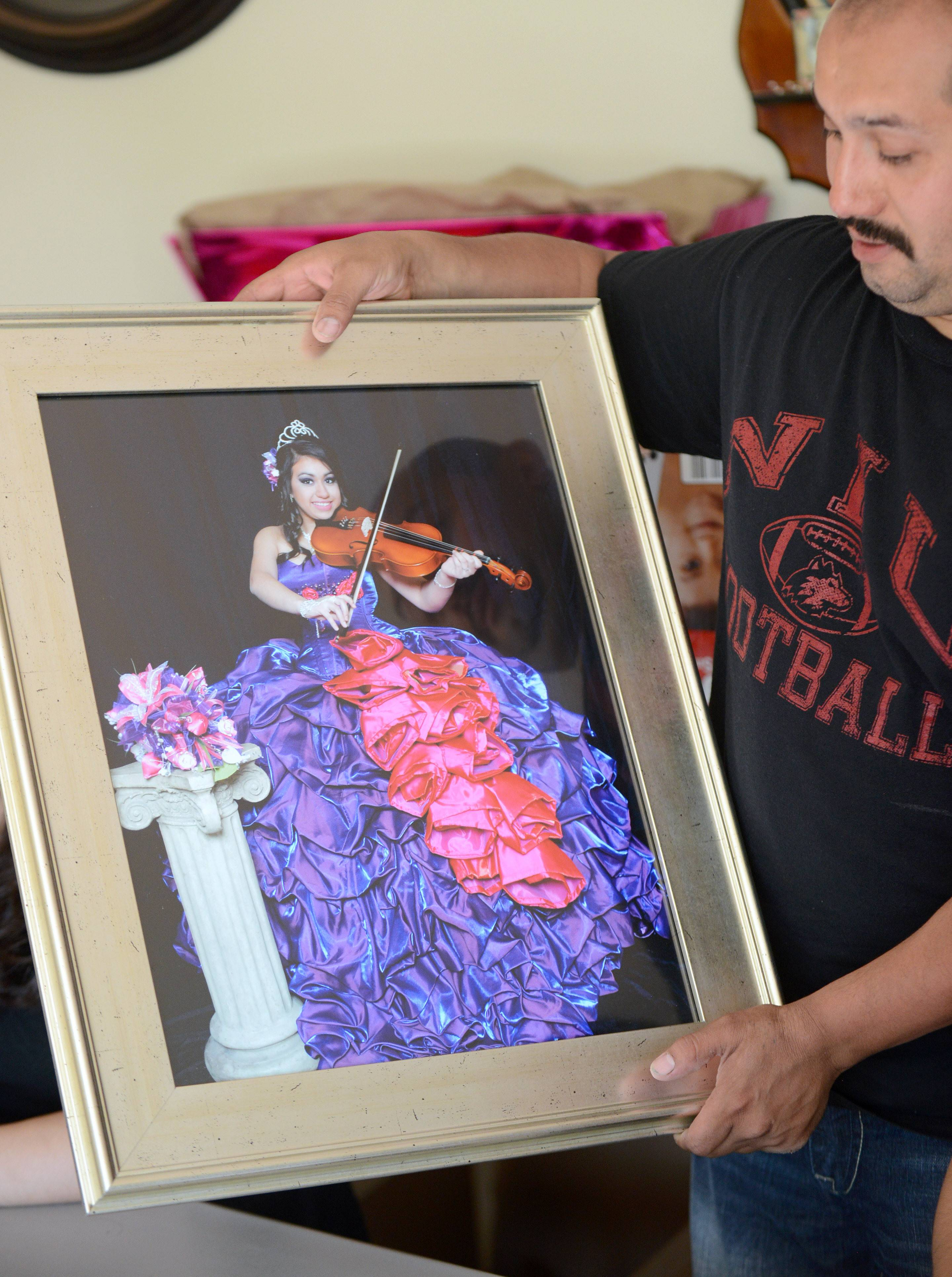 José Huerta shows a photo of his daughter in the quinceañera dress his wife, Brandy, won for her.