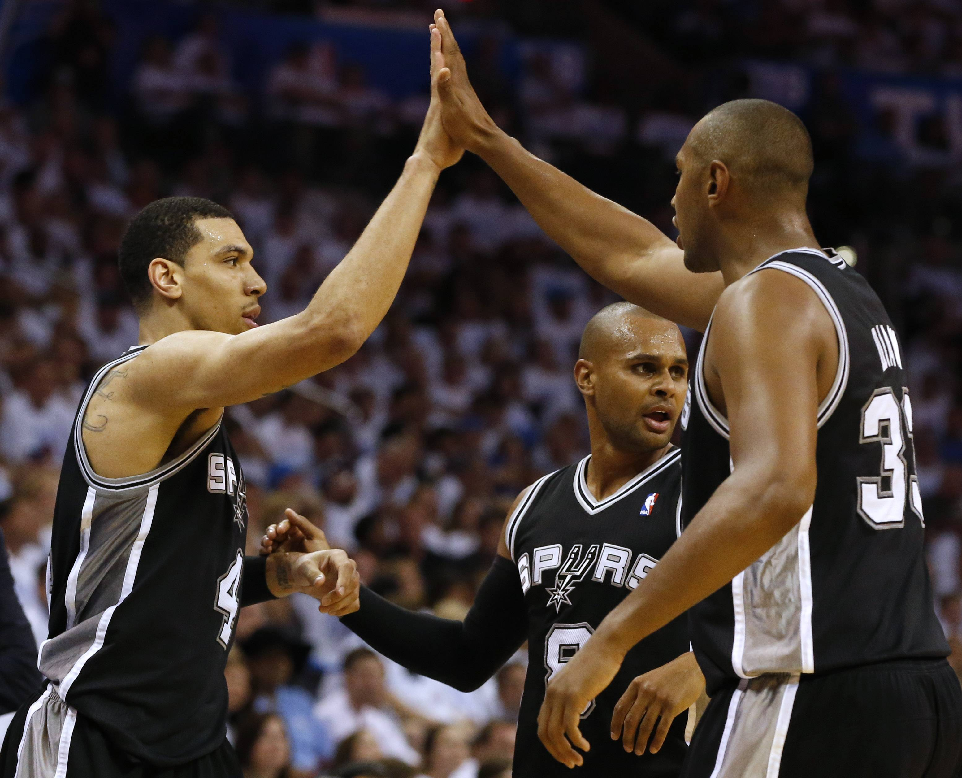 San Antonio's Danny Green, Patty Mills and Boris Diaw celebrate during the second half of Saturday's game against Oklahoma City. The Spurs beat the Thunder 112-107 in overtime to win the Western Conference finals in six games.