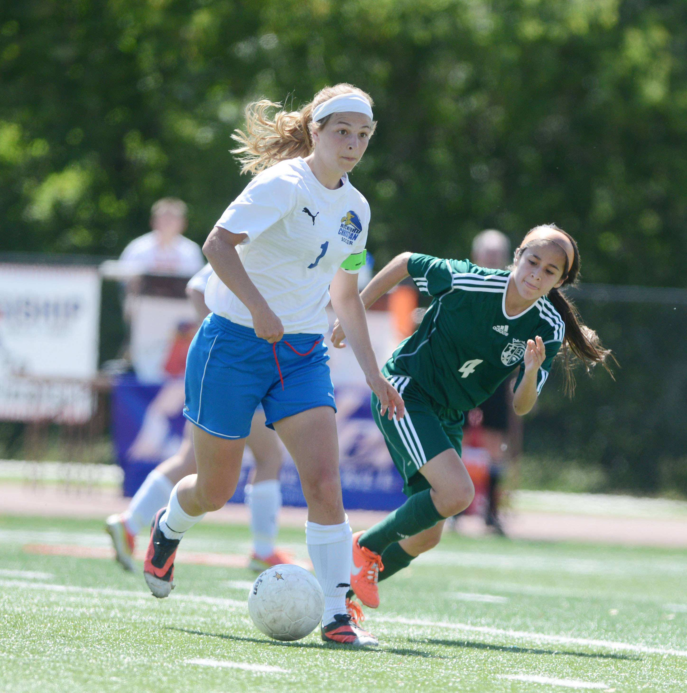 Haley Kittle of Rockford Christian and Monica Ramirez of St. Edward chase the ball during the Class 1A state girls soccer third place game Saturday.