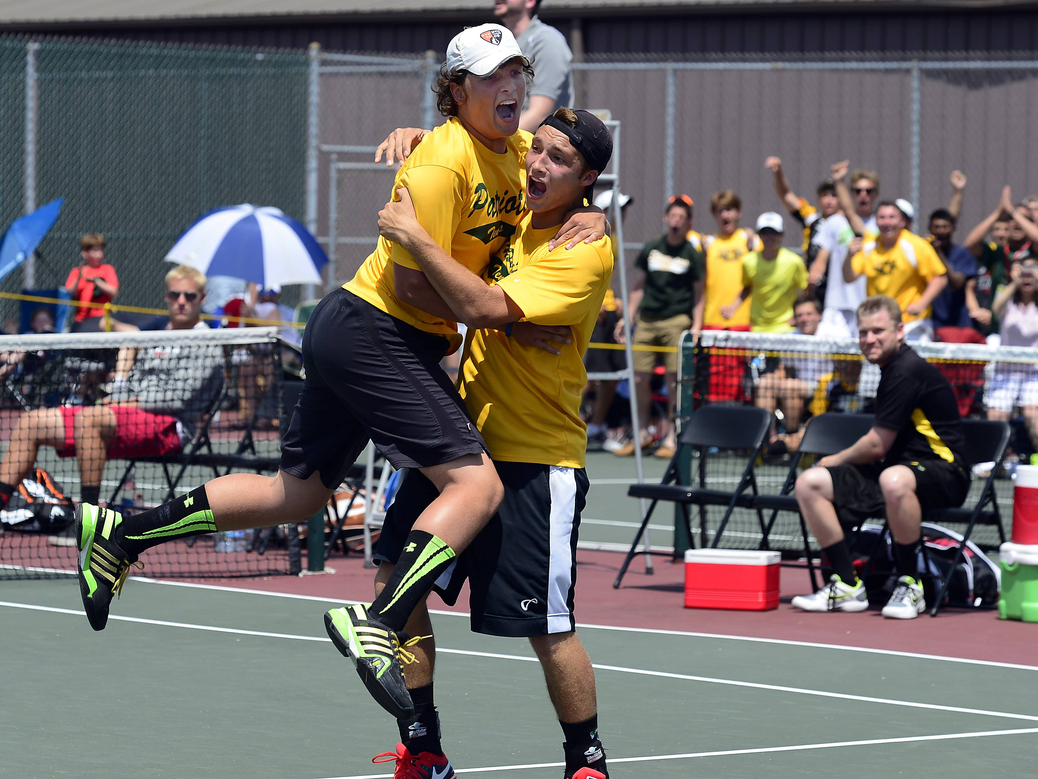 Stevenson's Andrew Komarov jumps into the arms teammate Colin Harvey as they wrap up a double state championship by topping Hinsdale Central's Lope Adelakun and Chase Hamilton at Hersey on Saturday afternoon.
