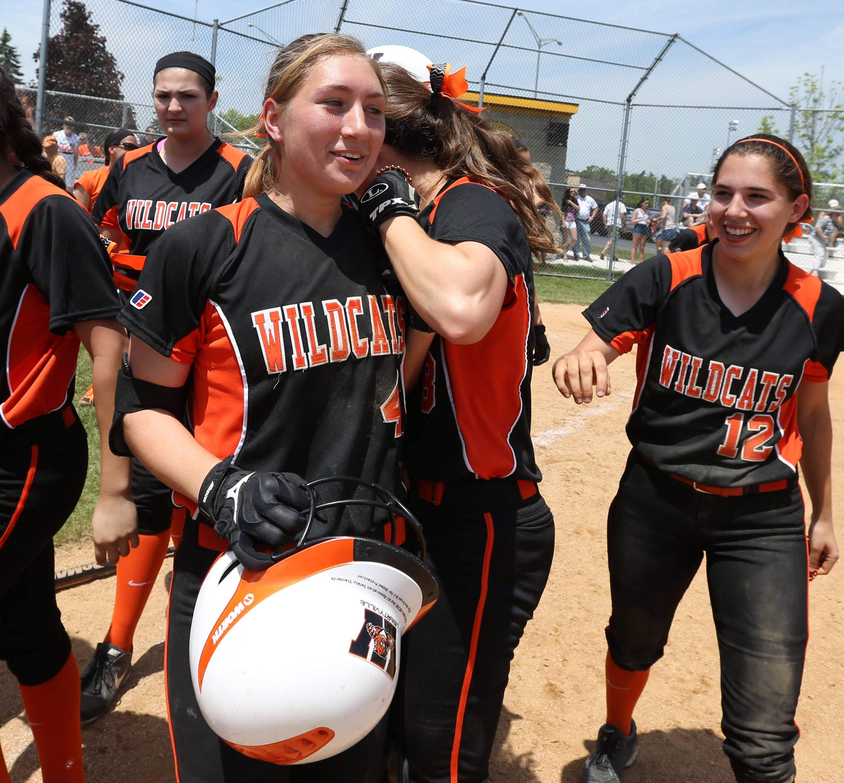 Libertyville's softball team rushes from the dugout to greet Tayler Oberman after her walk-off single against Carmel in the Class 4A Carmel softball regional final Saturday.