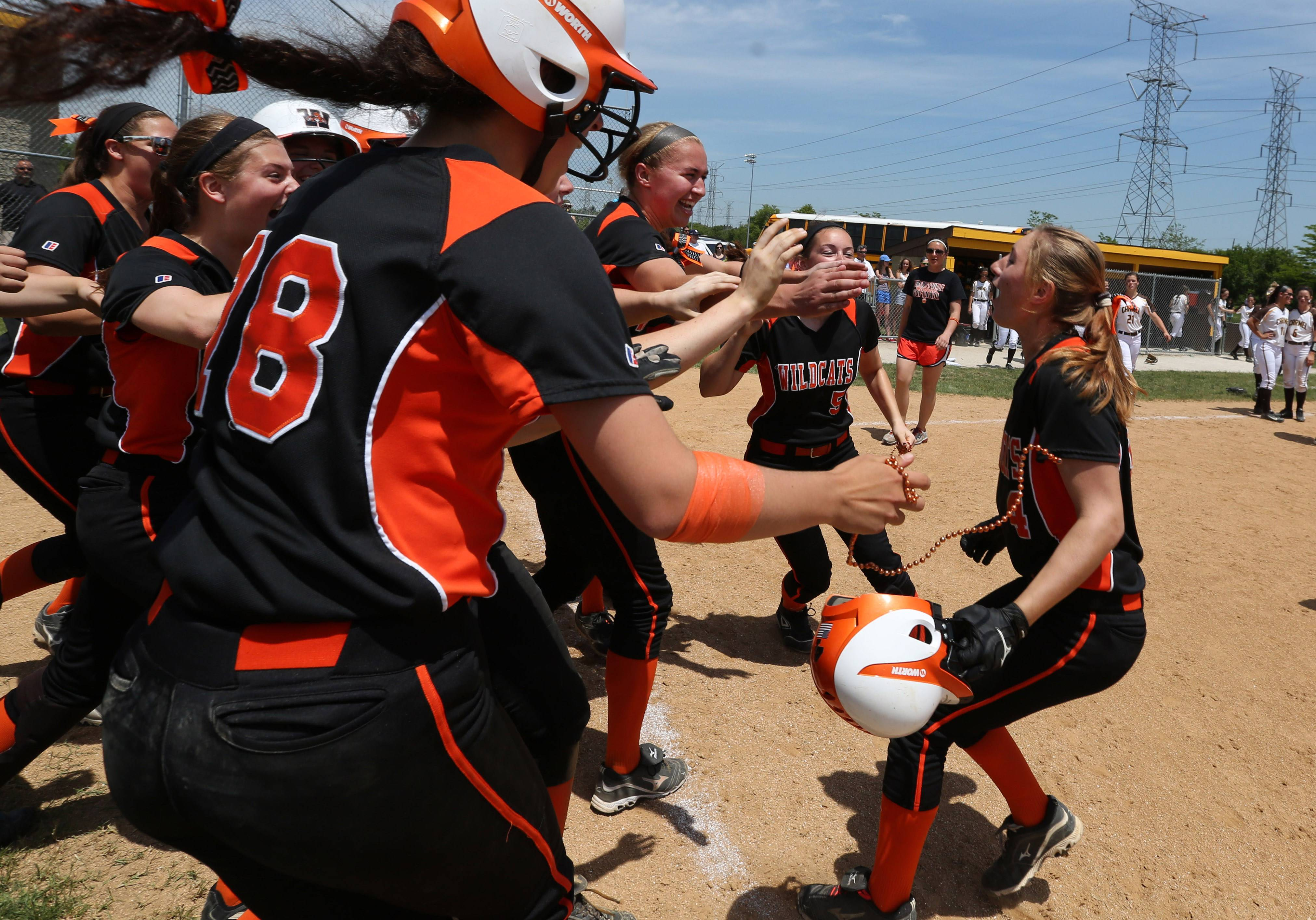 Libertyville's softball team rushes from the dugout to Tayler Oberman after her walk-off single against Carmel in the Class 4A Carmel softball regional final Saturday.