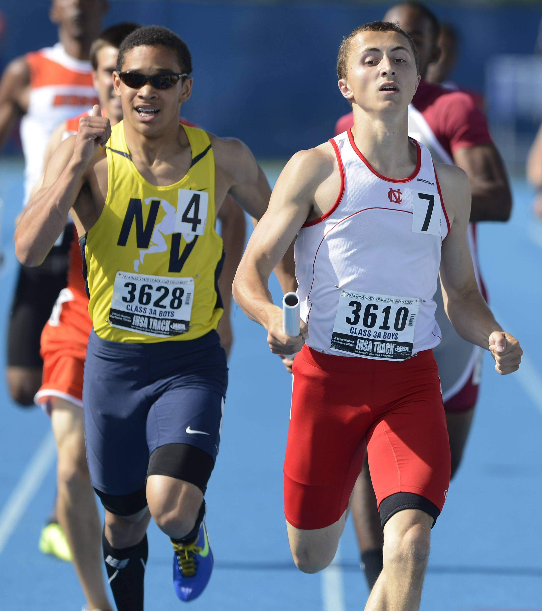 Neuqua Valley's Ty Moss, left, and Naperville Central's Sam Bransby cross the finish line in adjacent lanes while running in the 4x400-meter relay during the boys class 3A state track and field finals in Charleston Saturday.