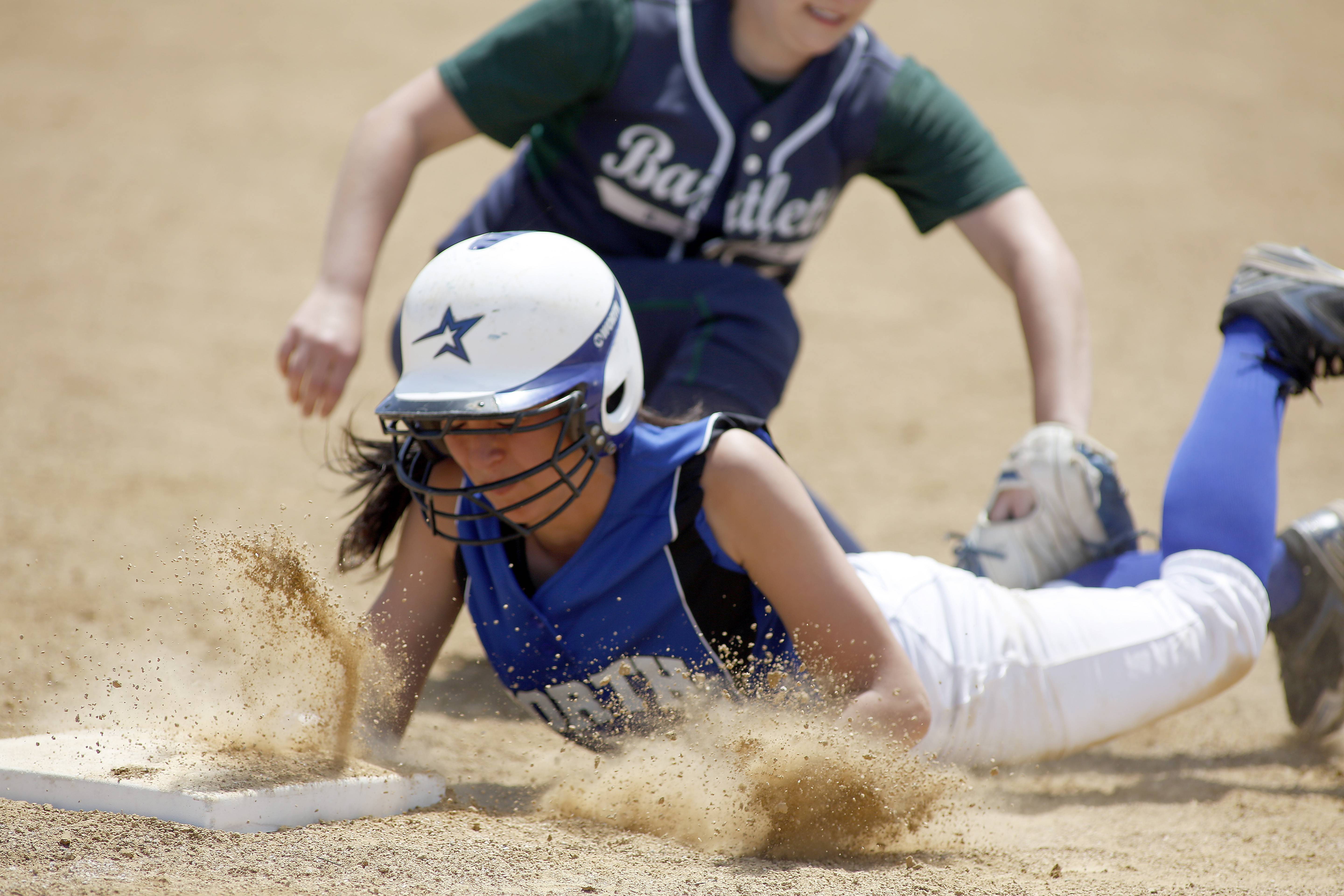 St. Charles North's Abi Ginther dives safely head first back into third as Bartlett's Sydney Johnson can't quite get the tag on her during the championship game of Class 4A Addison Trail regional Saturday.