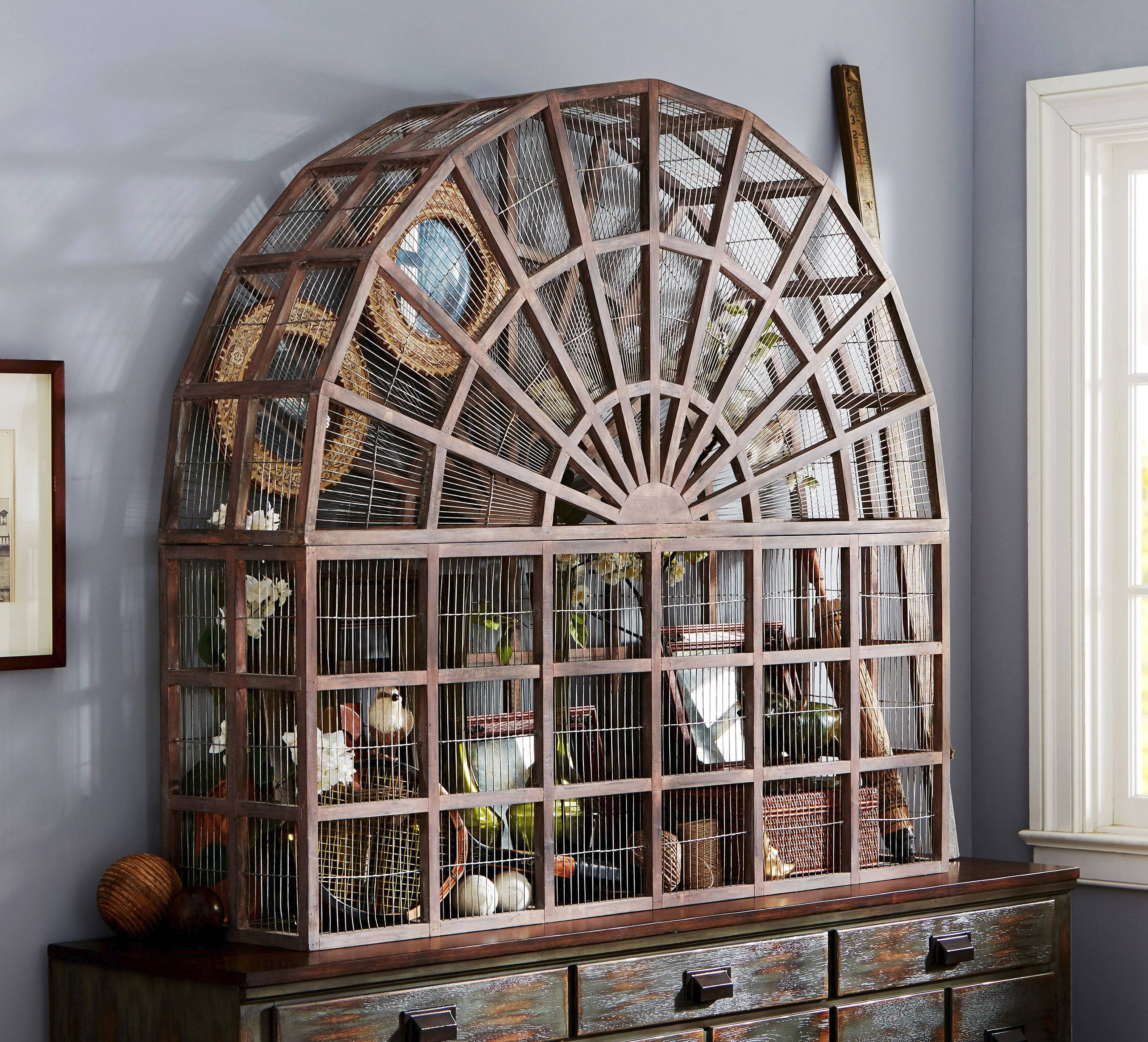 Pottery Barn's large Conservatory bird cage made of mahogany and wire is a statement piece due to its scale, and replicates similar designs of the Victorian era. It would look striking alone, or filled with elements of a personal collection, or even plants. Those drawn to 19th-century style may be happy to learn that vintage garden decor is a trend for spring and summer.