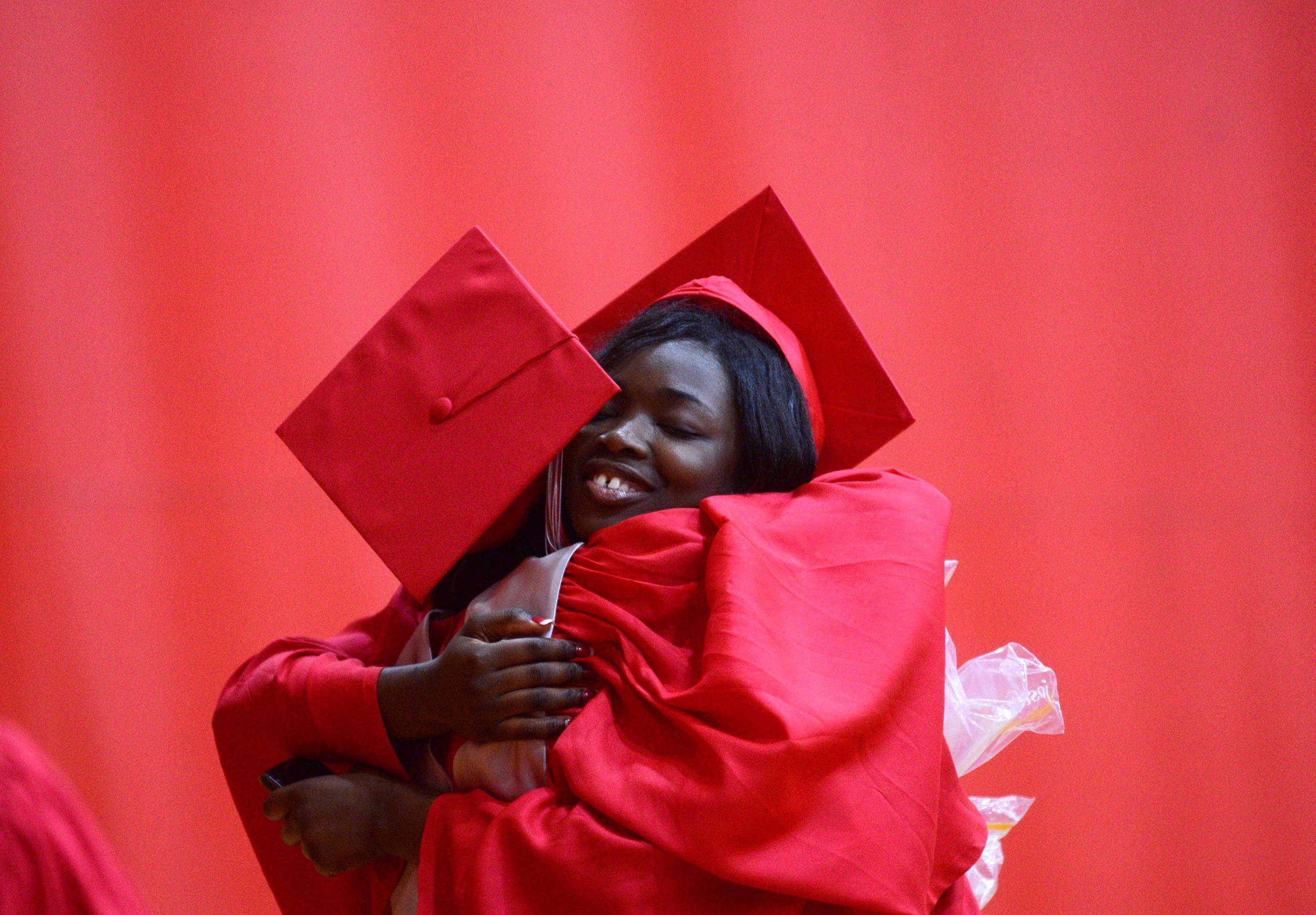 Debbie Adewusi, facing camera, receives a hug from Lenora Estes as they line up for the 131st commencement of Palatine High School on Sunday at the school.