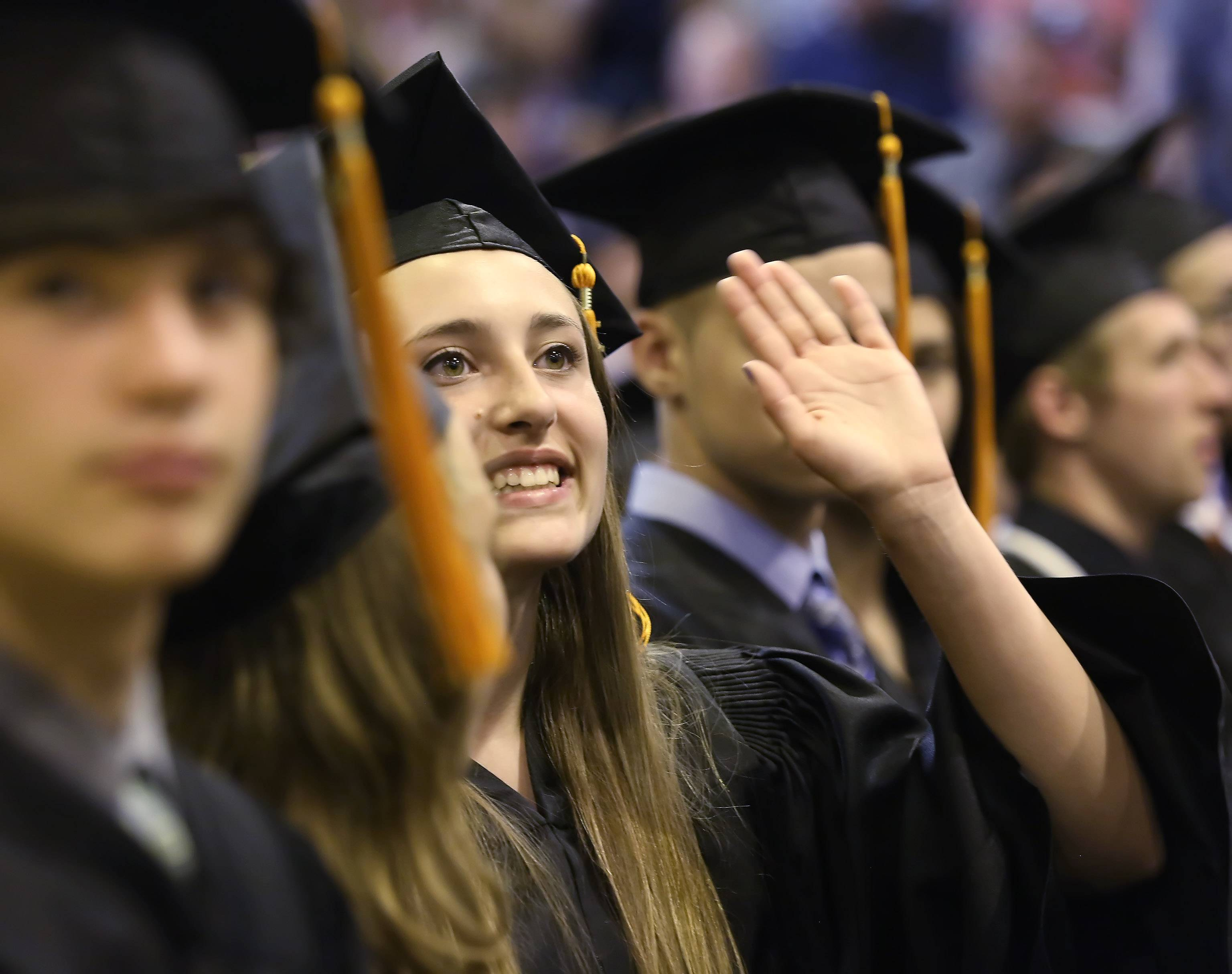 Carly Pisano waves to family and friends during the graduation ceremony Sunday at Hersey High School in Arlington Heights. There were 525 seniors who received diplomas at the school.