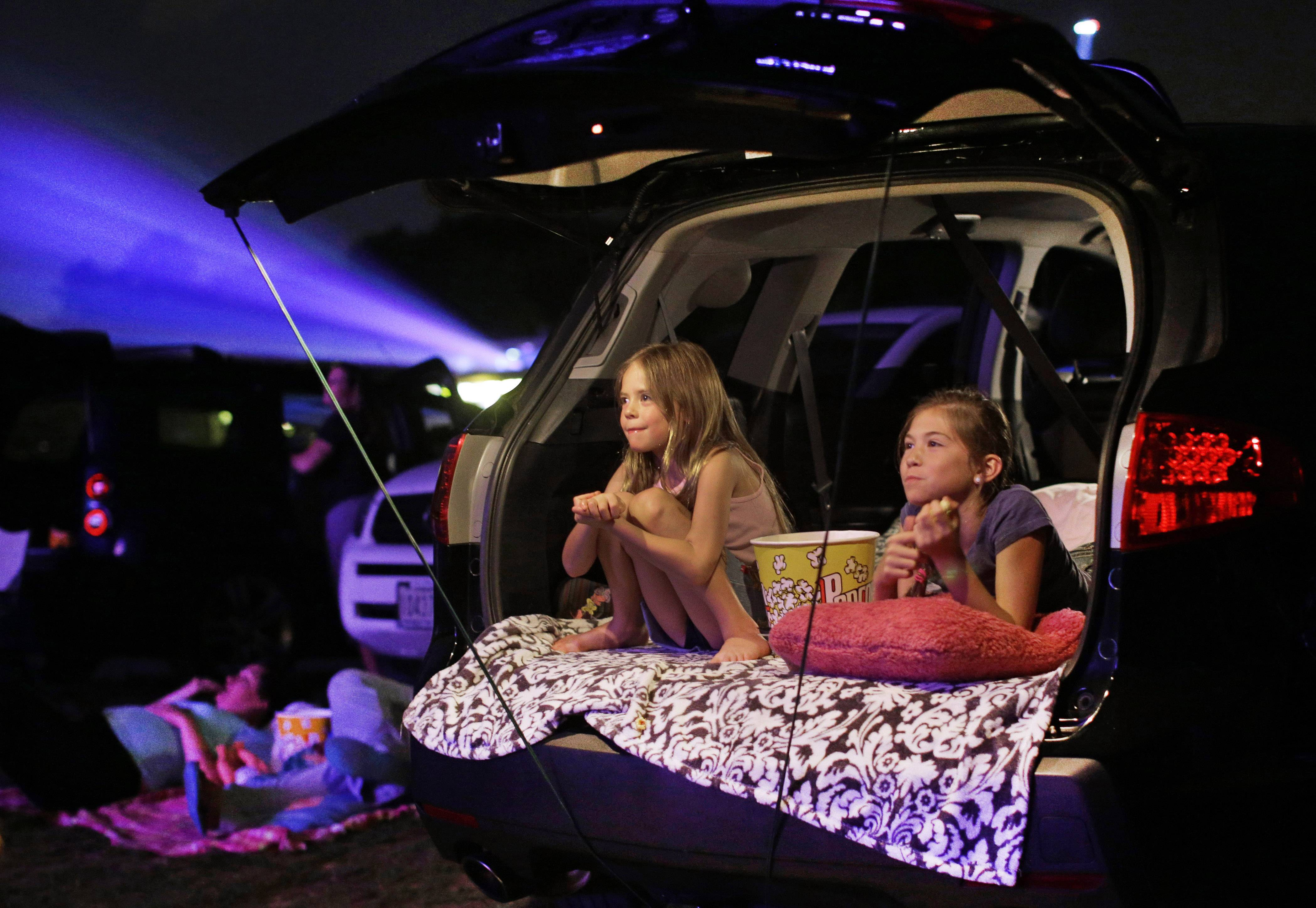 Maddie Essig, left, 10, watches a movie with her sister, Claire, 6, from the tailgate of their parents' vechicle at Bengies Drive-In Theatre in Middle River, Md. Drive-in movie theaters, which numbered 4,300 in 1957, have dwindled to just 350.