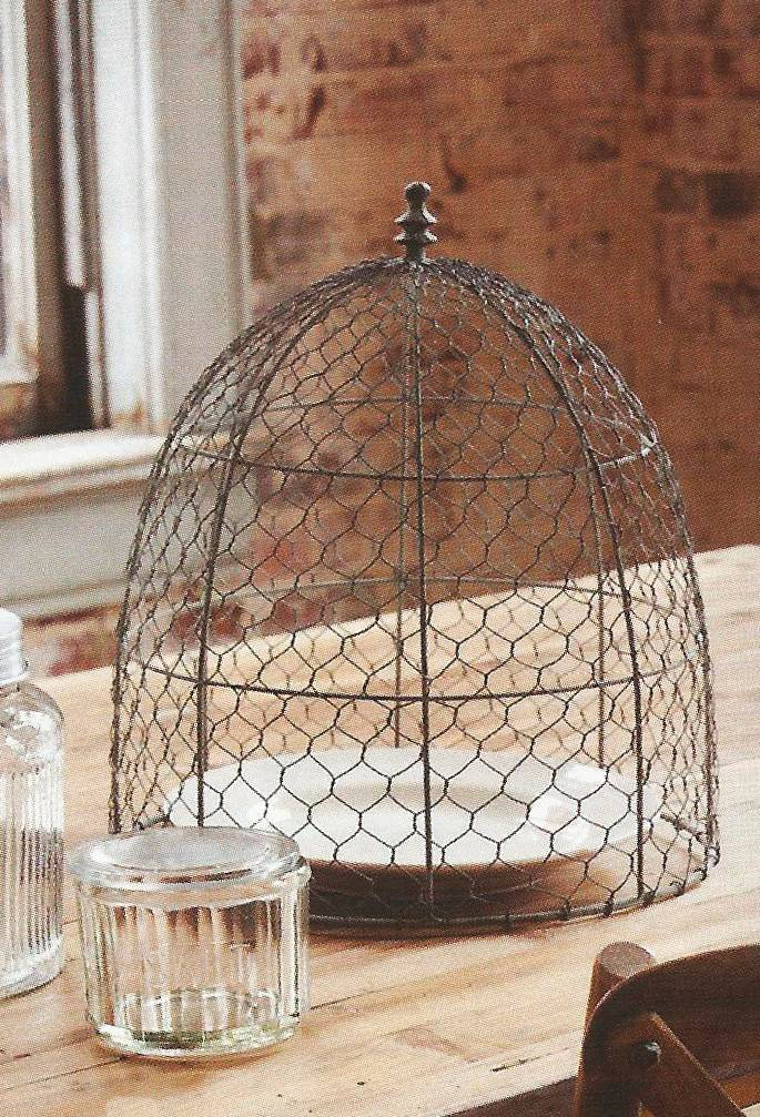 Farmhouse Wares' chicken wire cloche adds vintage flair to a small plant or tabletop display.