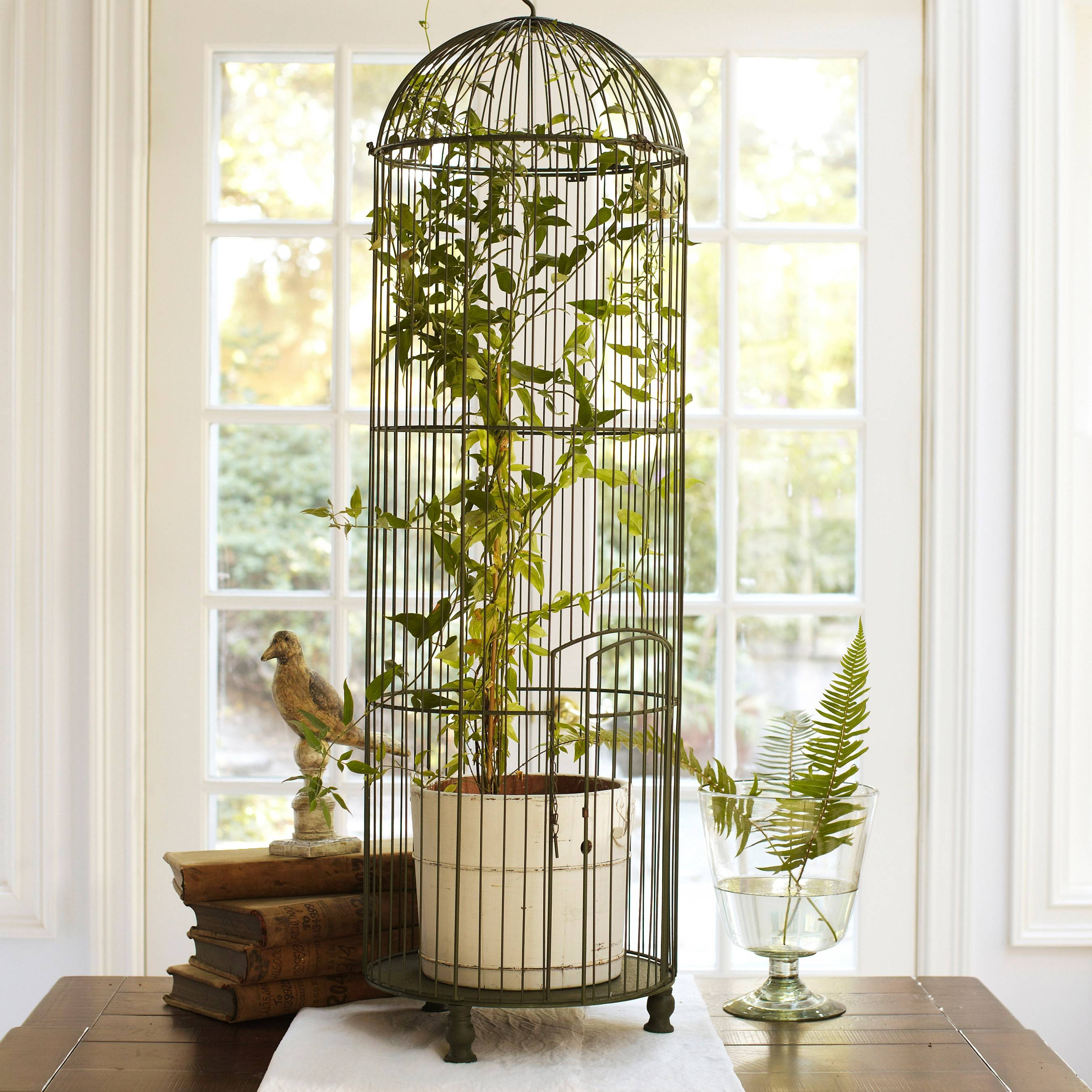 Pottery Barn's tall wire birdcage in a distressed green painted wire can be filled with a tall plant or just used as a decorative tabletop accessory.  Victorians were fond of birds in all iterations, from illustrations to textile motifs to aviaries large and small.